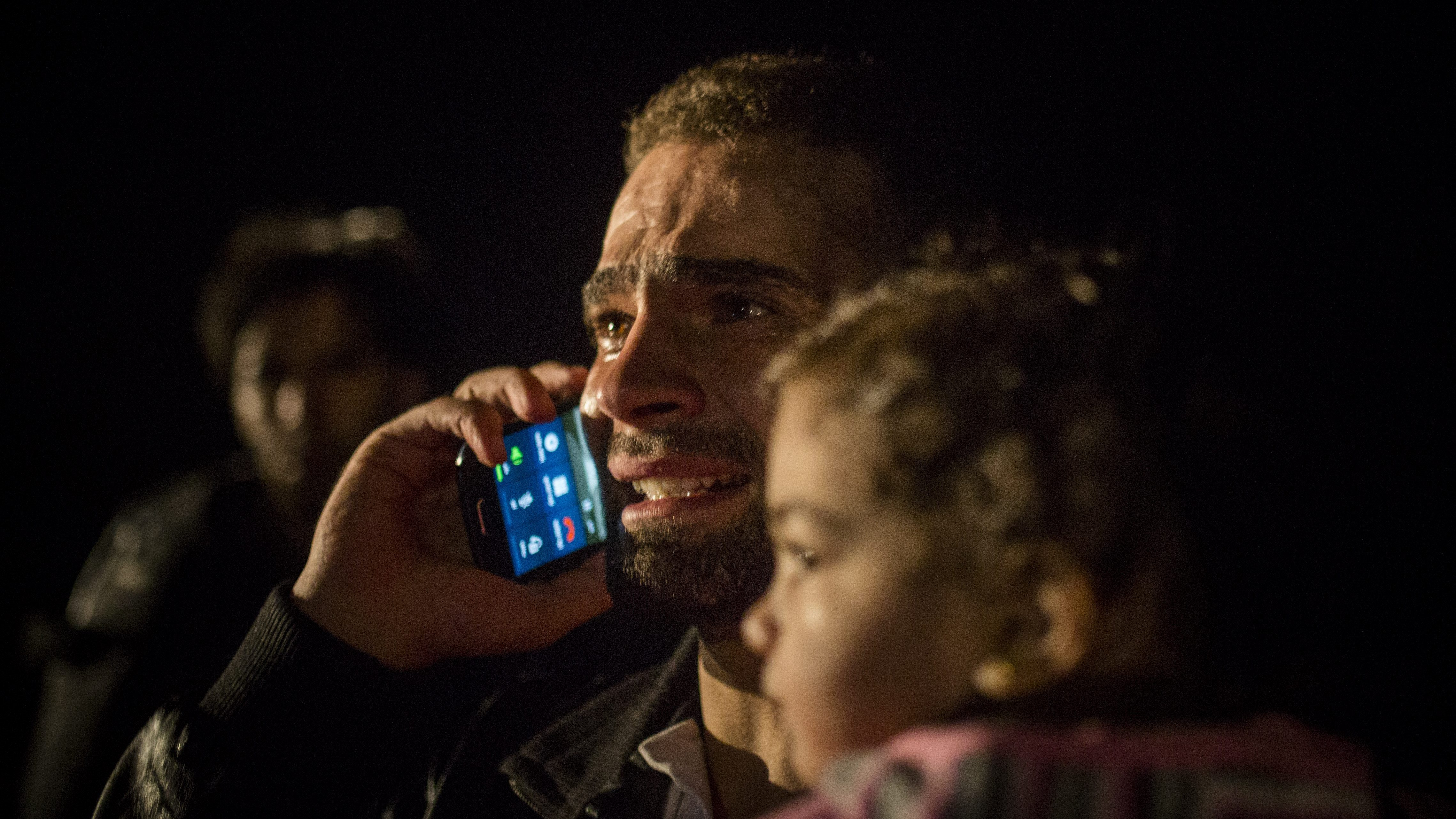 A Syrian man holds his daughter while making a phone call immediately after his arrival on a dinghy from the Turkish coast to the northeastern Greek island of Lesbos, Thursday, Oct. 8, 2015. More than 500,000 people have arrived in the European Union this year, seeking sanctuary or jobs and sparking the EU's biggest refugee emergency in decades. (AP Photo/Santi Palacios)