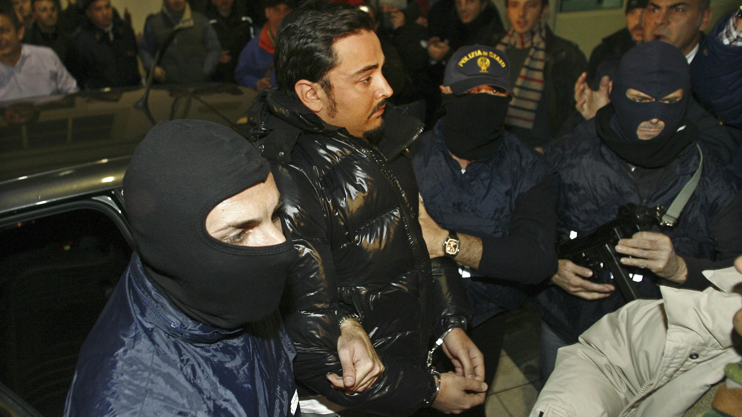 Masked Italian police officers accompany Sicilian Mafia suspect Giovanni Nicchi (C) to a police station in Palermo December 5, 2009.