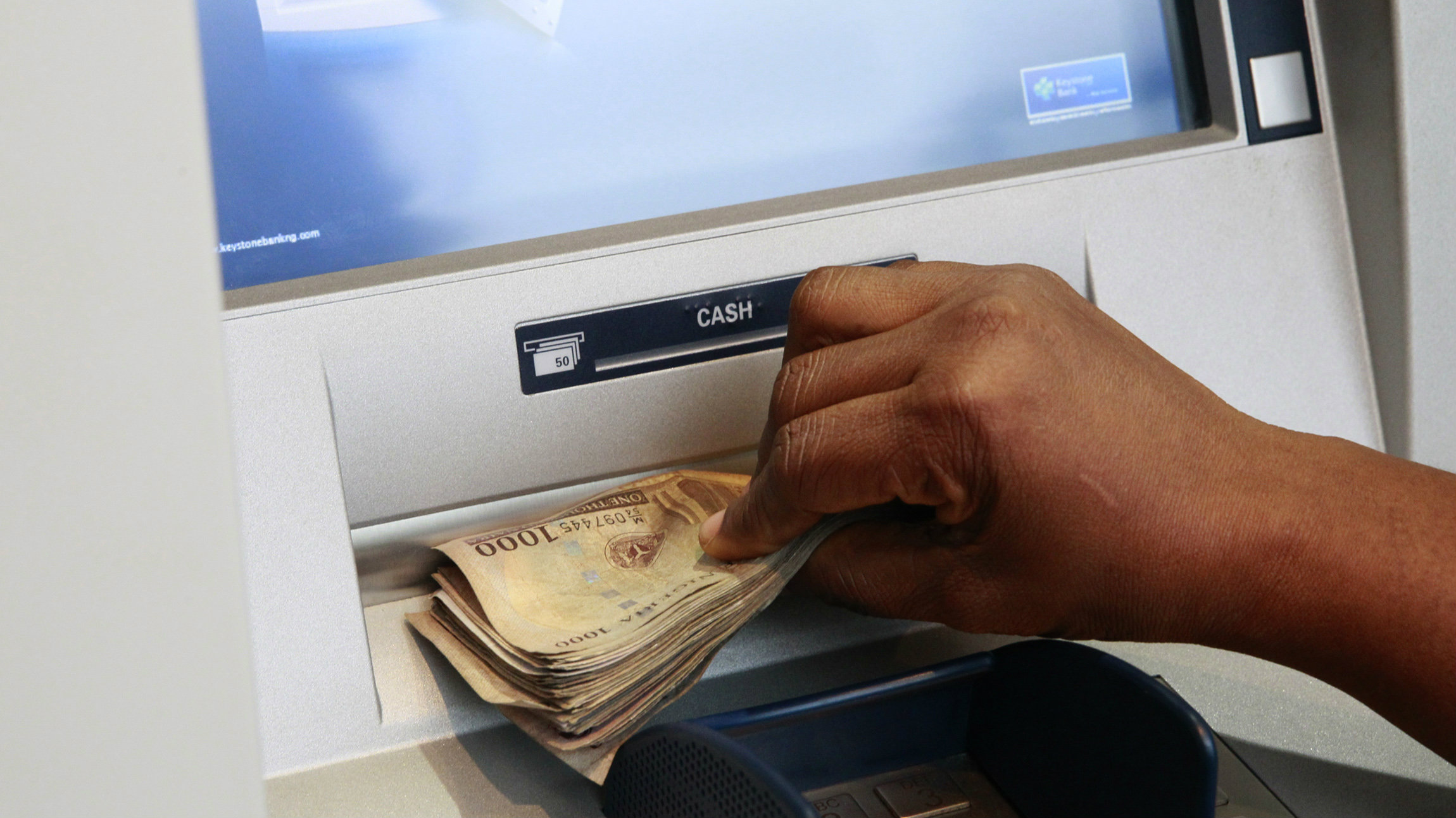 A woman takes Nigerian Naira from a bank's automated teller machine (ATM) in Ikeja district in the commercial capital Lagos November 12, 2014.