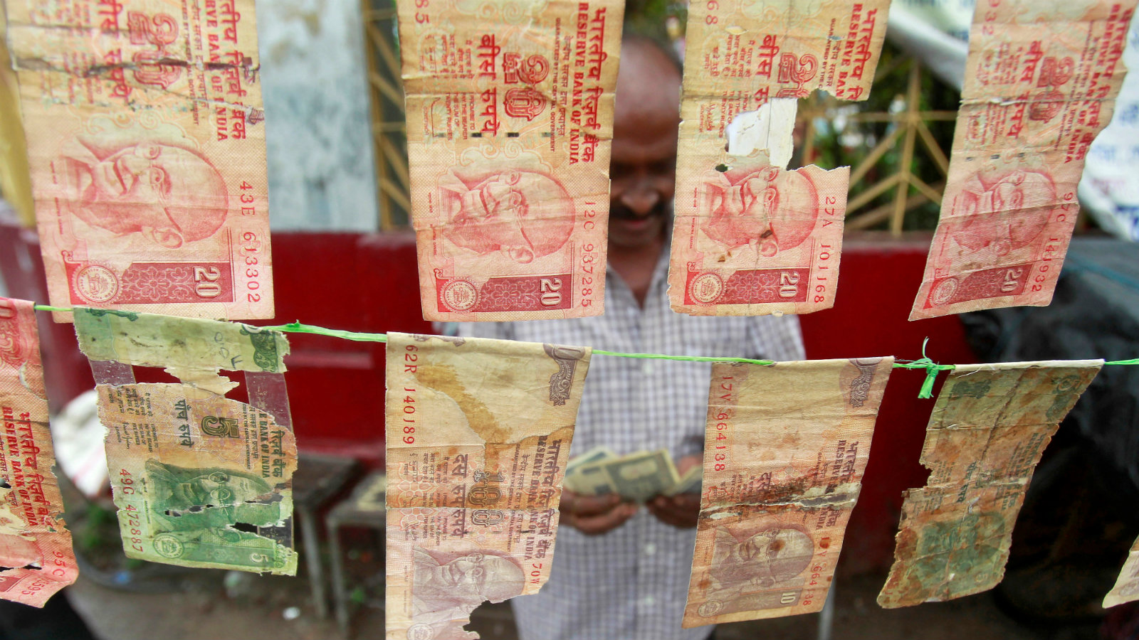 A roadside currency exchange vendor counts money at his stall in Agartala, India May 19, 2016.