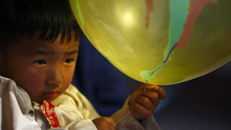 "A Tibetan boy dressed in traditional attire holds a balloon as he observes the function organised to mark ""Losar"" or the Tibetan New Year at Tibetan Refugee Camp in Lalitpur February 19, 2015. REUTERS/Navesh Chitrakar"