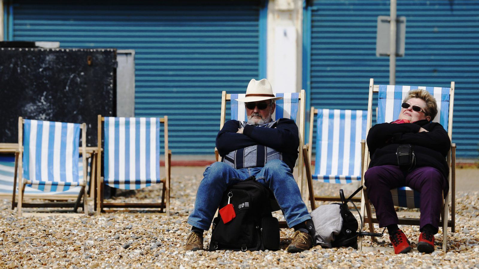 An elderly couple sits on deck chairs on a cool afternoon