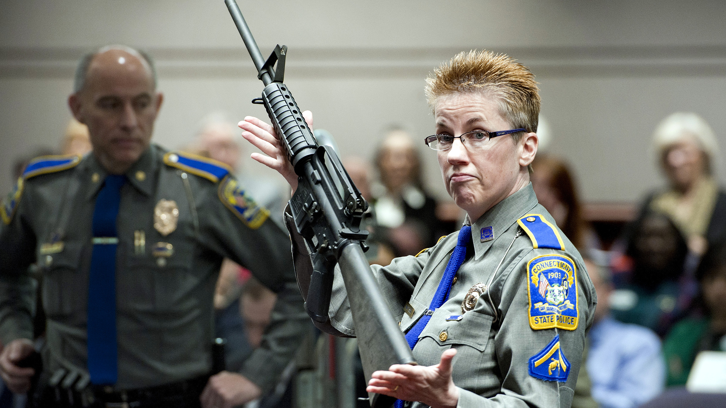 Firearms Training Unit Detective Barbara J. Mattson of the Connecticut State Police holds up a Bushmaster AR-15 rifle, the same make and model of gun used by Adam Lanza in the Sandy Hook School shooting, for a demonstration during a hearing of a legislative subcommittee reviewing gun laws, at the Legislative Office Building in Hartford, Conn., Monday, Jan. 28, 2013. The parents of children killed in the Newtown school shooting called for better enforcement of gun laws Monday at the legislative hearing.