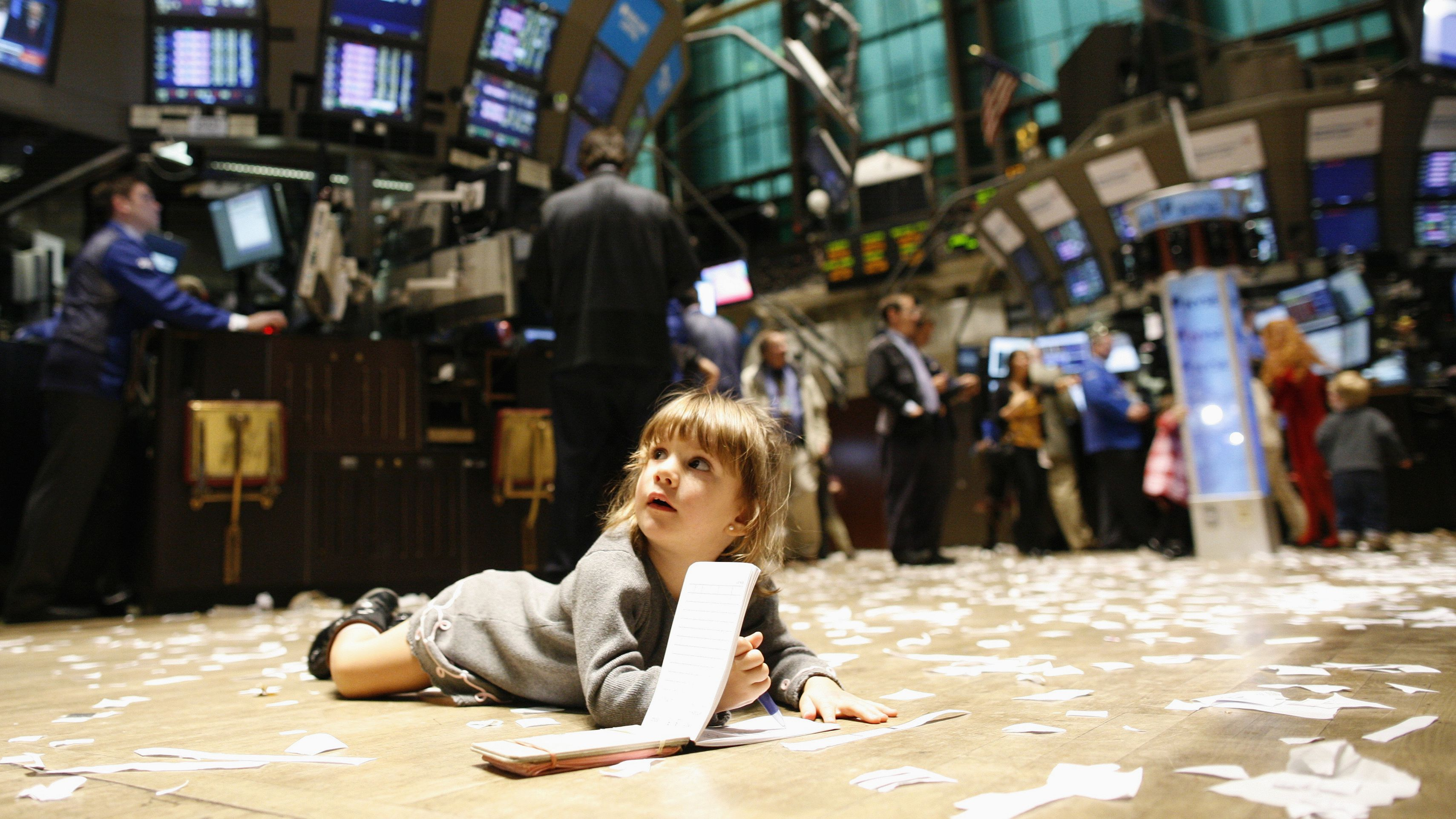 Gabriella Liloia lies on the trading floor, during kid's day at the New York Stock Exchange November 27, 2009. The New York Stock Exchange allowed children on the floor during the shortened trading day. REUTERS/Brendan McDermid