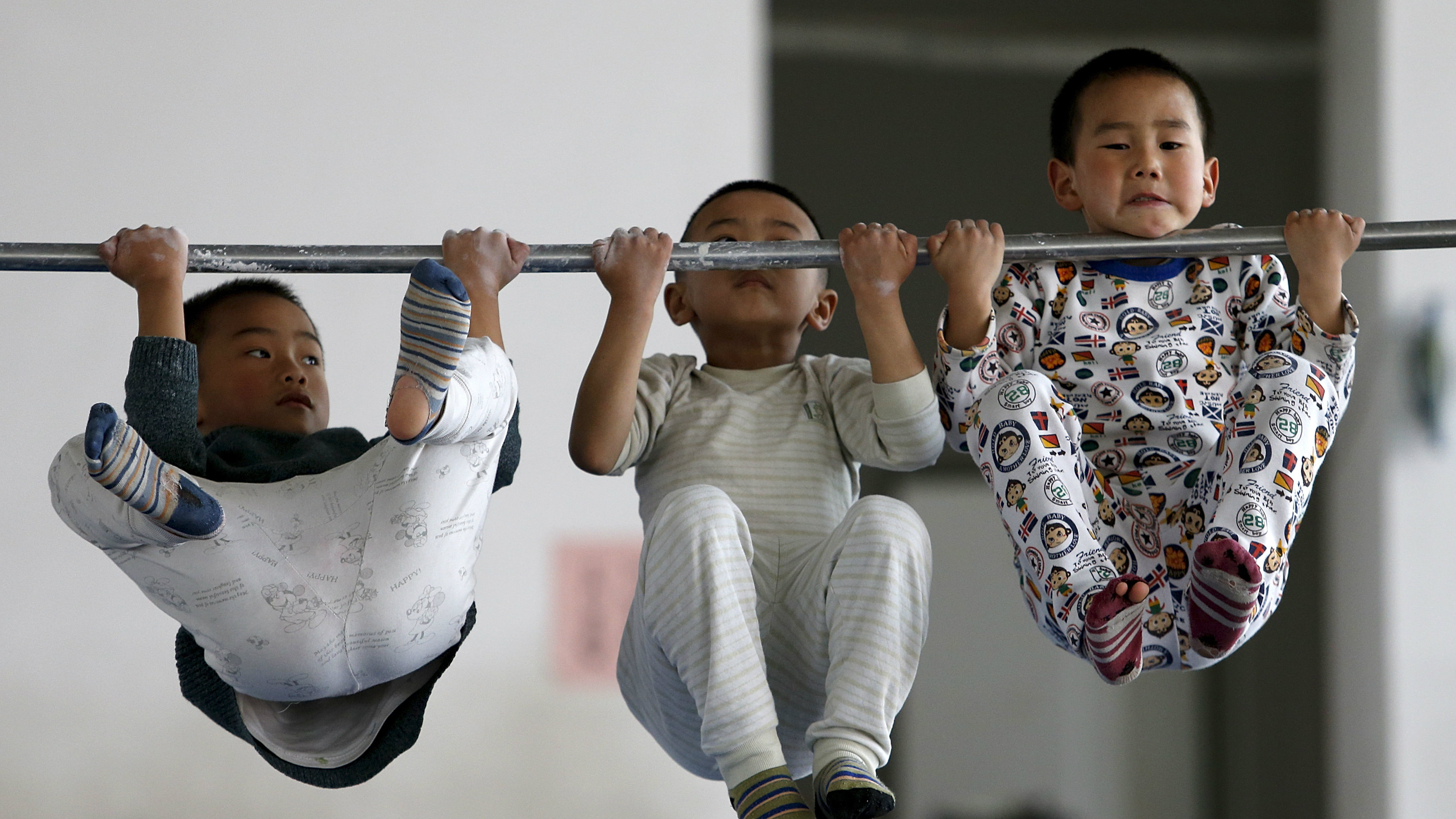 Young gymnasts practice pull-up on a bar at a gymnasium of a sports school in Jiaxing, Zhejiang province April 11, 2015. REUTERS/William Hong TPX IMAGES OF THE DAY  CHINA OUT. NO COMMERCIAL OR EDITORIAL SALES IN CHINA