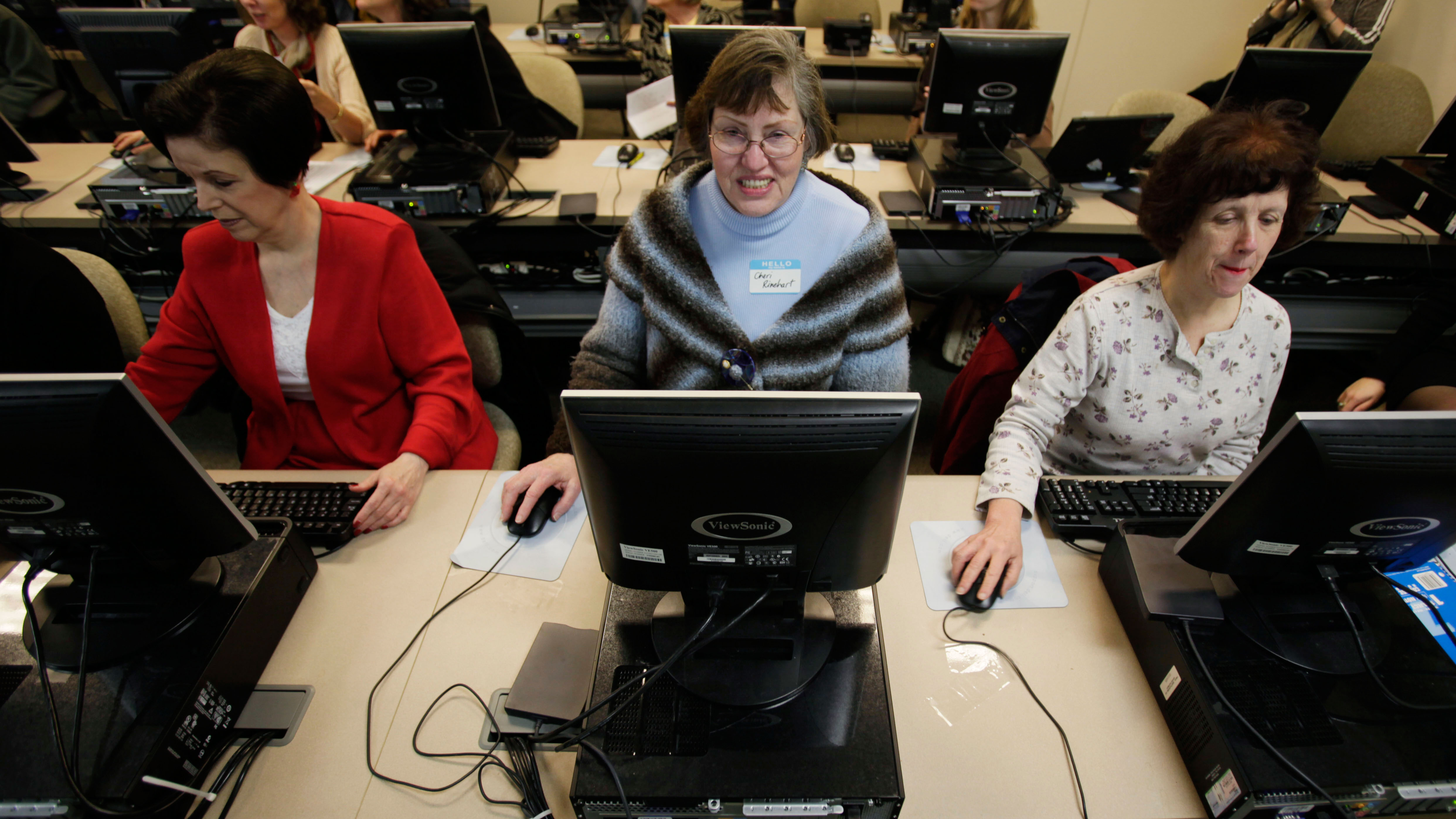 Sue Carter, left, Cheri Rinehart, center, and Loraine Terpening, right, work on computers, Monday, April 13, 2009, in a training lab at a WorkSource office in downtown Seattle, as they wait to hear about a program that will provide more than 30,000 training vouchers to workers and those seeking work in Washington state to pay for training courses ranging from basic technology literacy to intermediate-level technology skills. The program is a partnership between Microsoft, the state's Employment Security Department and the Workforce Development Council of Seattle-King County. (AP Photo/Ted S. Warren)