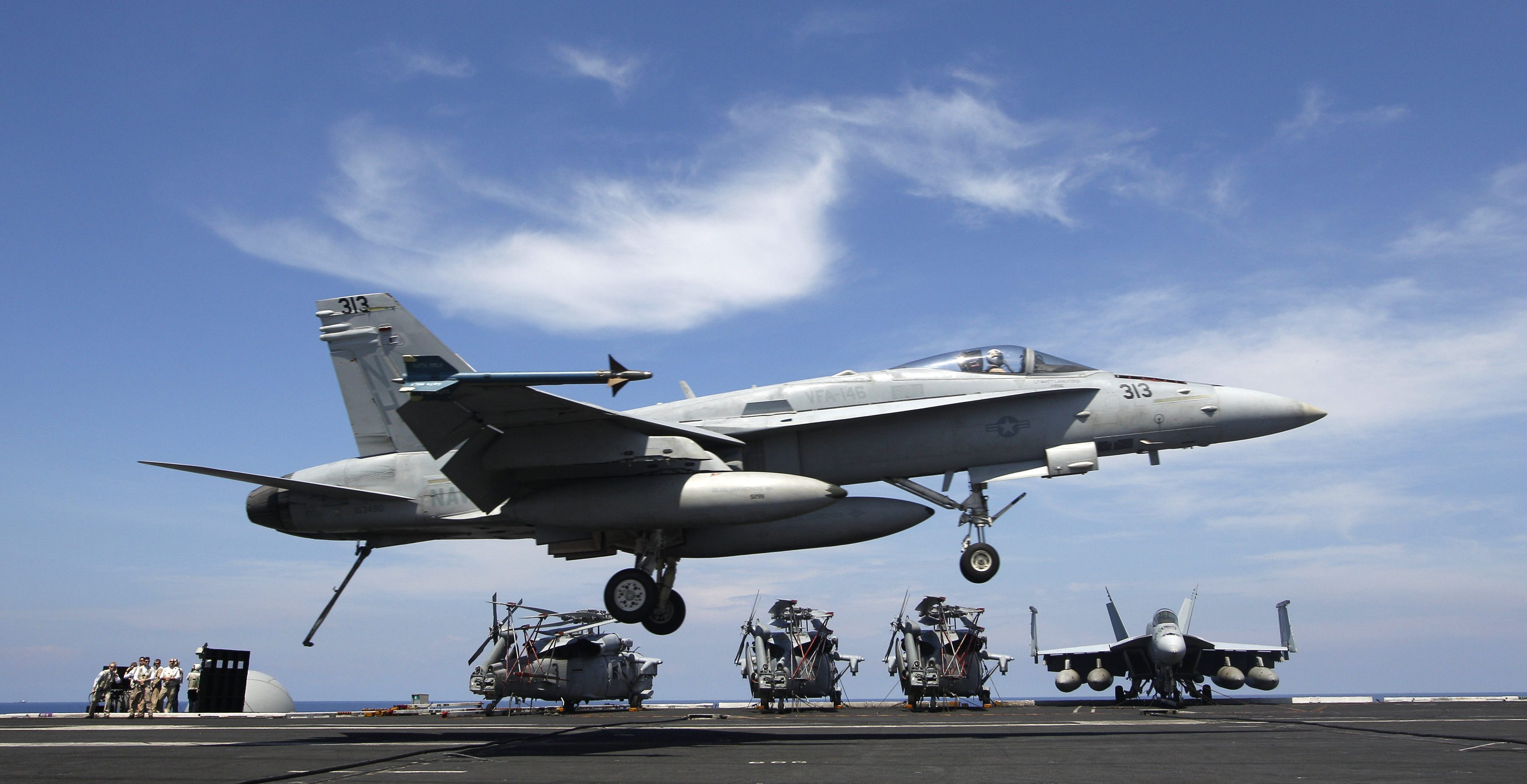 US Navy F/A-18C aircraft prepares to land on the runway of the USS Nimitz aircraft carrier during a tour of the ship in the South China Sea