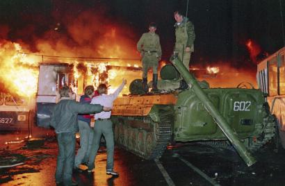 A trolley bus that was used by anti-coup demonstrators to block the exit of Soviet armored personnel carriers from the area near the Soviet Foreign Ministry office burns during a verbal confrontation between some demonstrators and Soviet soldiers standing atop an armored vehicle in downtown Moscow, Soviet Union