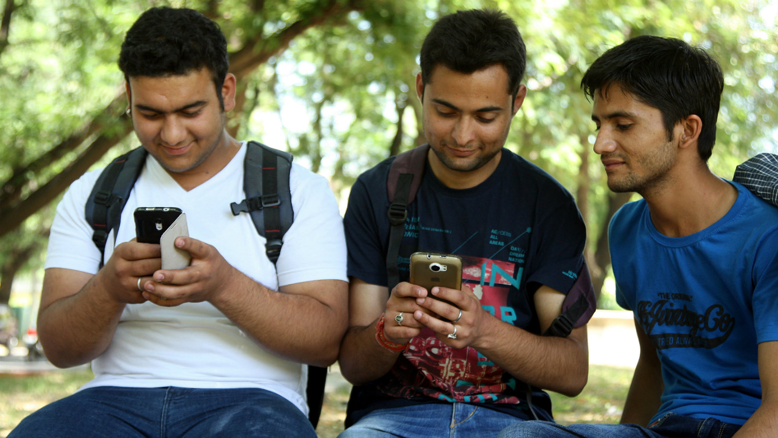 Indian students use their mobile phones to send a Short Message Service (SMS) on their prepaid cell phone in Jammu, the winter capital of Kashmir, India, 21 May 2014. Jammu and Kashmir government lifted the four year old ban on Short Messaging Services (SMS) on prepaid cell phone subscribers in the state. In June 2010, the State government had imposed a ban on the SMS in the State following a widespread unrest in the Kashmir valley, an official spokesman said.