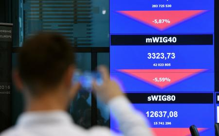 A man watches a board showing the WIG20 index at the Warsaw Stock Exchange in Poland, on June 24. The biggest WSE indices dropped by almost 10 per cent at the start of the session after Great Britain has voted to leave. (EPA/Radek Pietruszka)