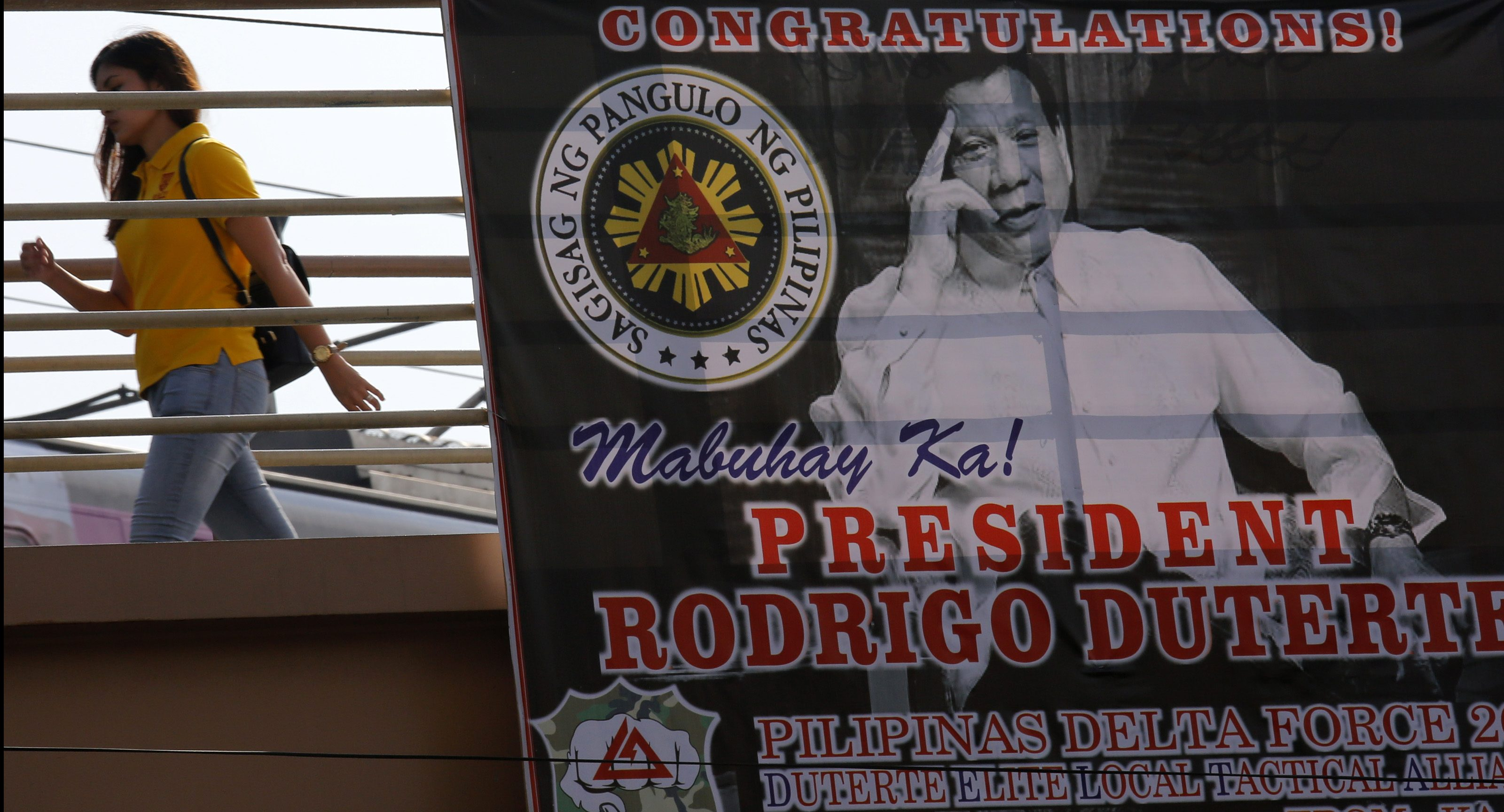 epa05397127 A President Duterte greeting poster hangs on an overpass pedestrain lane leading to the Malacanang presidential palace on the day before President-elect Rodrigo Duterte's inauguration in Manila, Philippines, 29 June 2016. Filipino President-elect Rodrigo Duterte said he will seek to reinstate the death penalty in the country for retribution against criminals, according to local media reports. Duterte has declared a war on drugs and encouraged local police forces to intensify their anti-drug operations. Duterte is set to take his seat as the 16th President of the Republic of the Philippines on 30 June.  EPA/FRANCIS R. MALASIG
