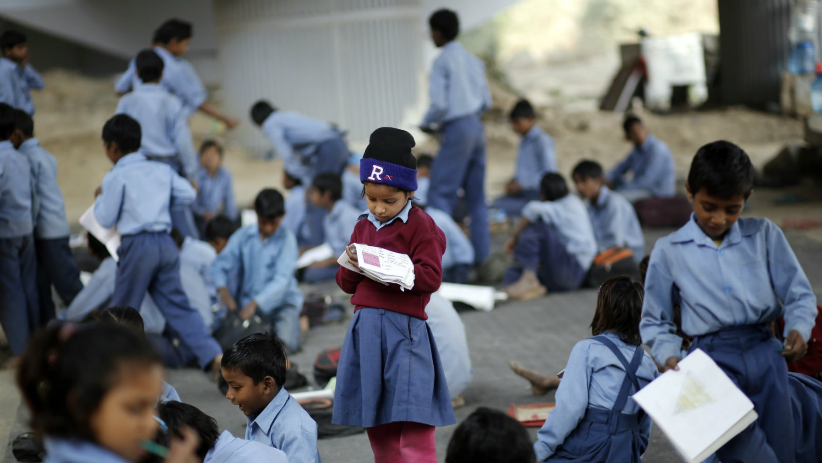 A schoolgirl reads from a textbook at an open-air school in New Delhi November 20, 2014. Picture taken November 20.