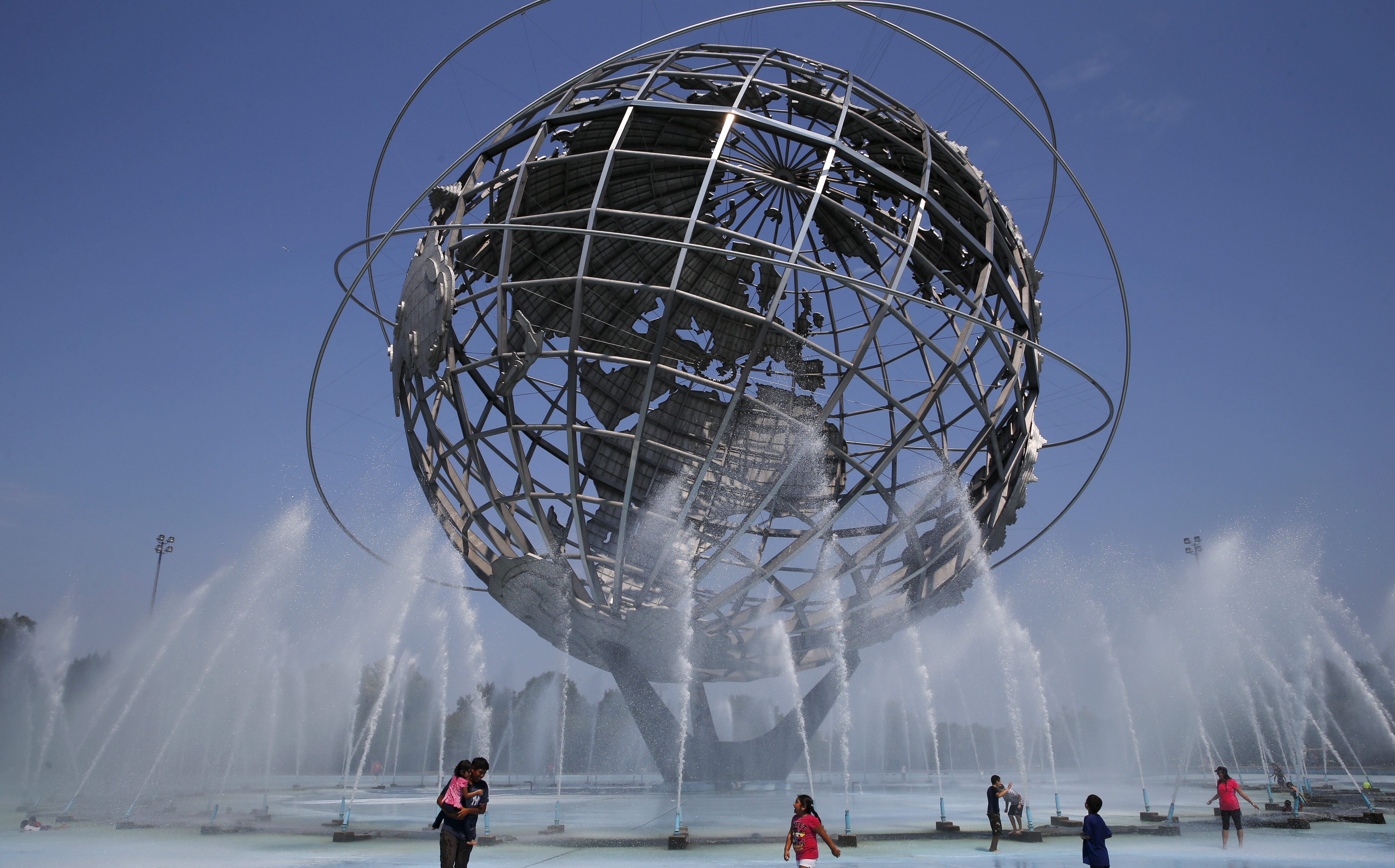 People cool off in the water at the Unisphere at Flushing Meadows Corona Park in the Queens borough of New York August 18, 2015.