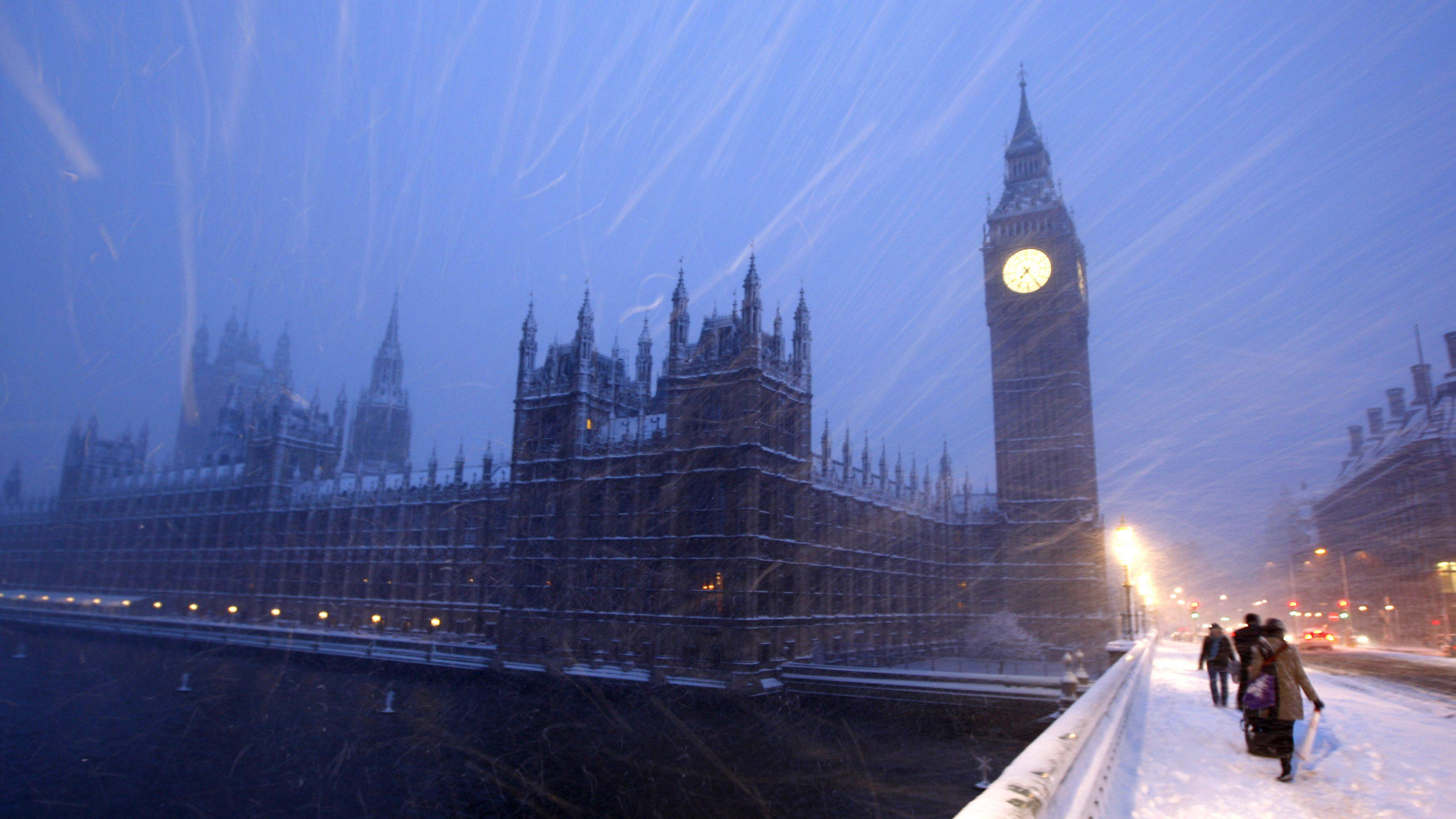 Pedestrians walk across Westminster Bridge as snow falls in central London