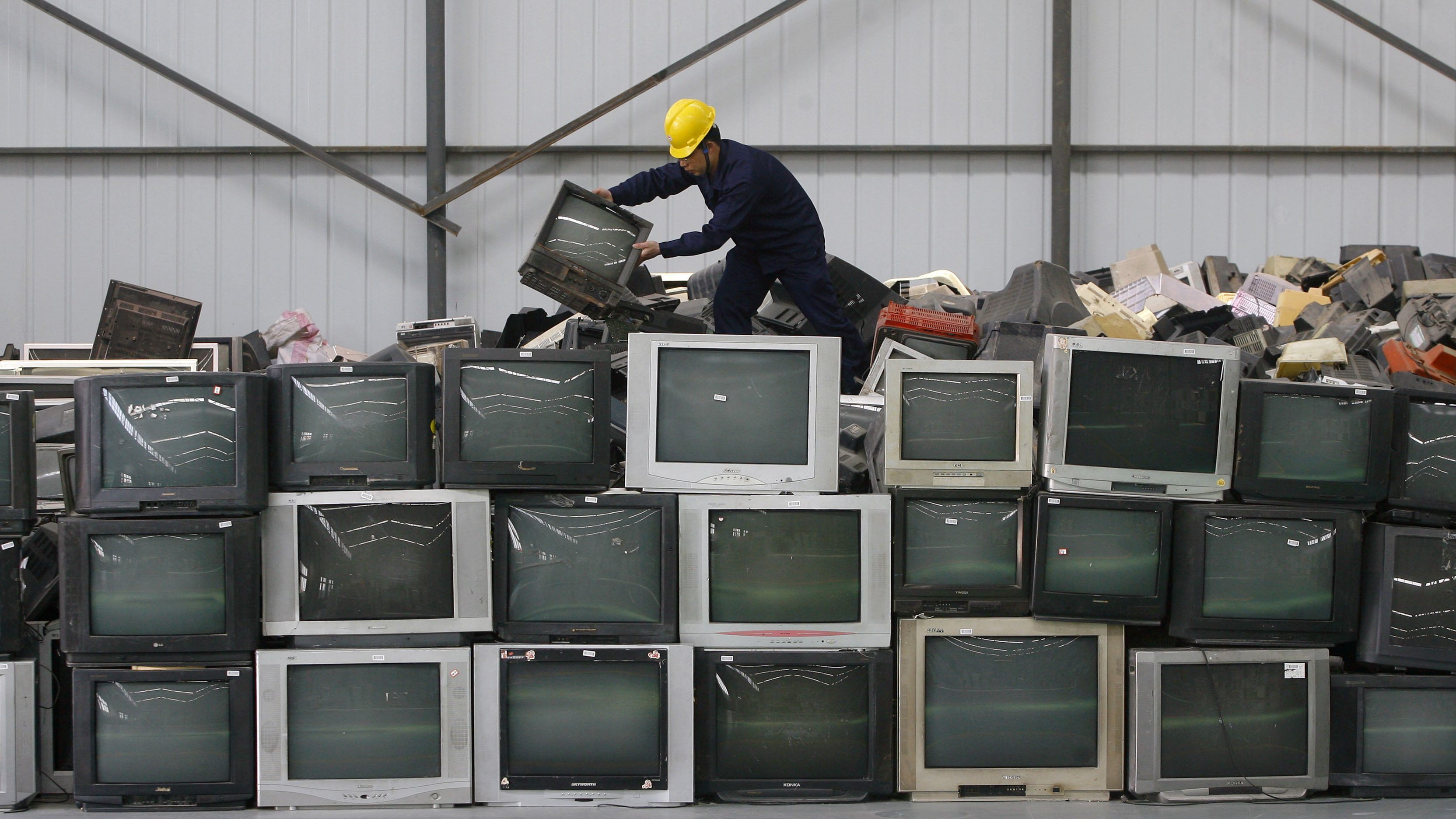 An employee arranges discarded televisions at a newly opened electronic waste recycling factory in Wuhan, Hubei province March 29, 2011. According to the U.S. Environmental Protection Agency (EPA), e-waste is the fastest growing commodity in the waste stream, with a growth rate five times that of other parts of the business such as industrial waste. The burgeoning middle classes in fast-growth China and India mean there are more computers and mobiles, adding to e-cycling growth.