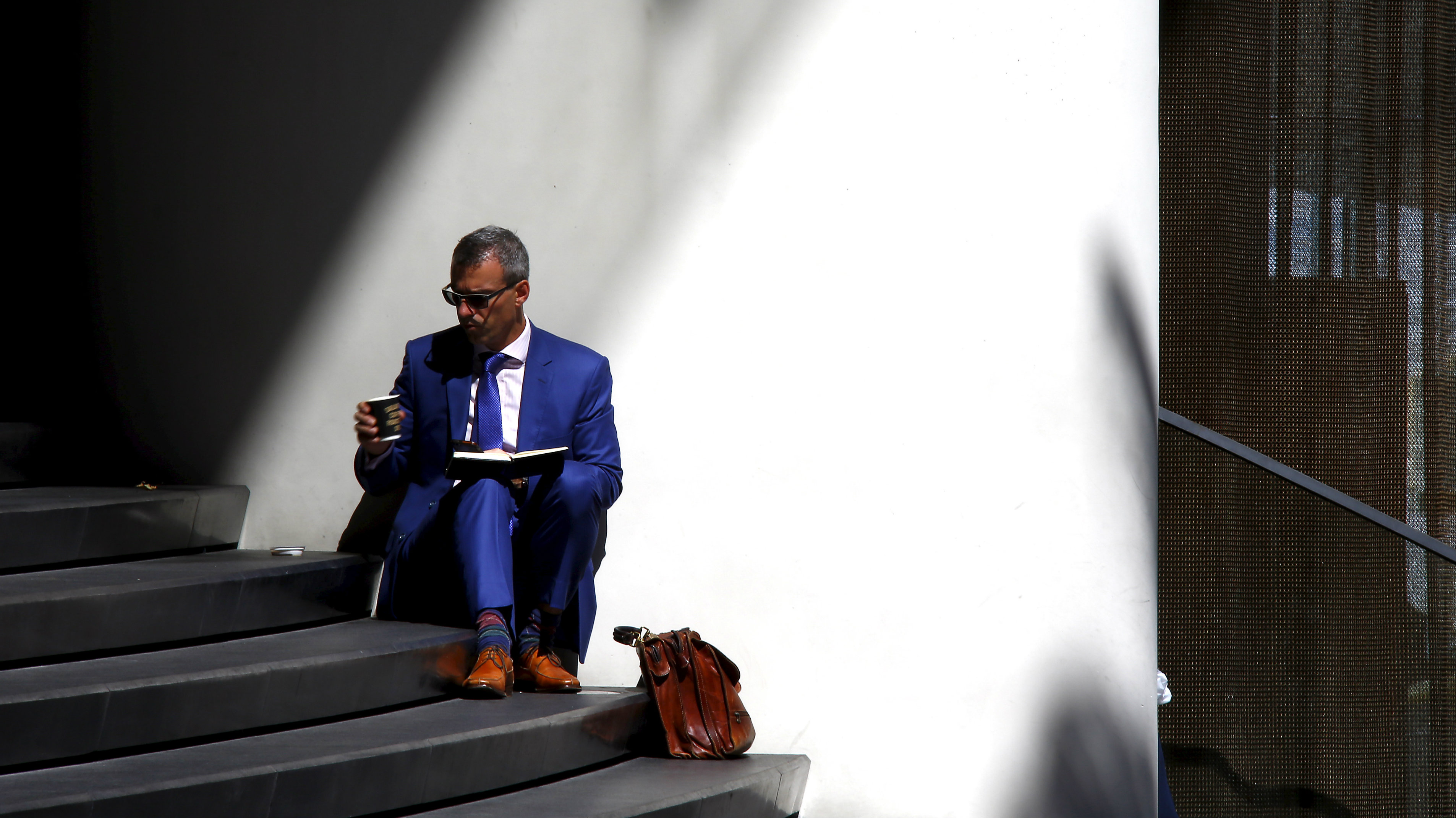 A businessman drinks coffee as he sits on the steps of an office building in central Sydney, Australia, March 23, 2016. Australian job advertisements in newspapers and on the Internet inched ahead in March, a potential sign demand for labour had peaked after a very strong 2015. Picture taken March 23, 2016. REUTERS/David Gray