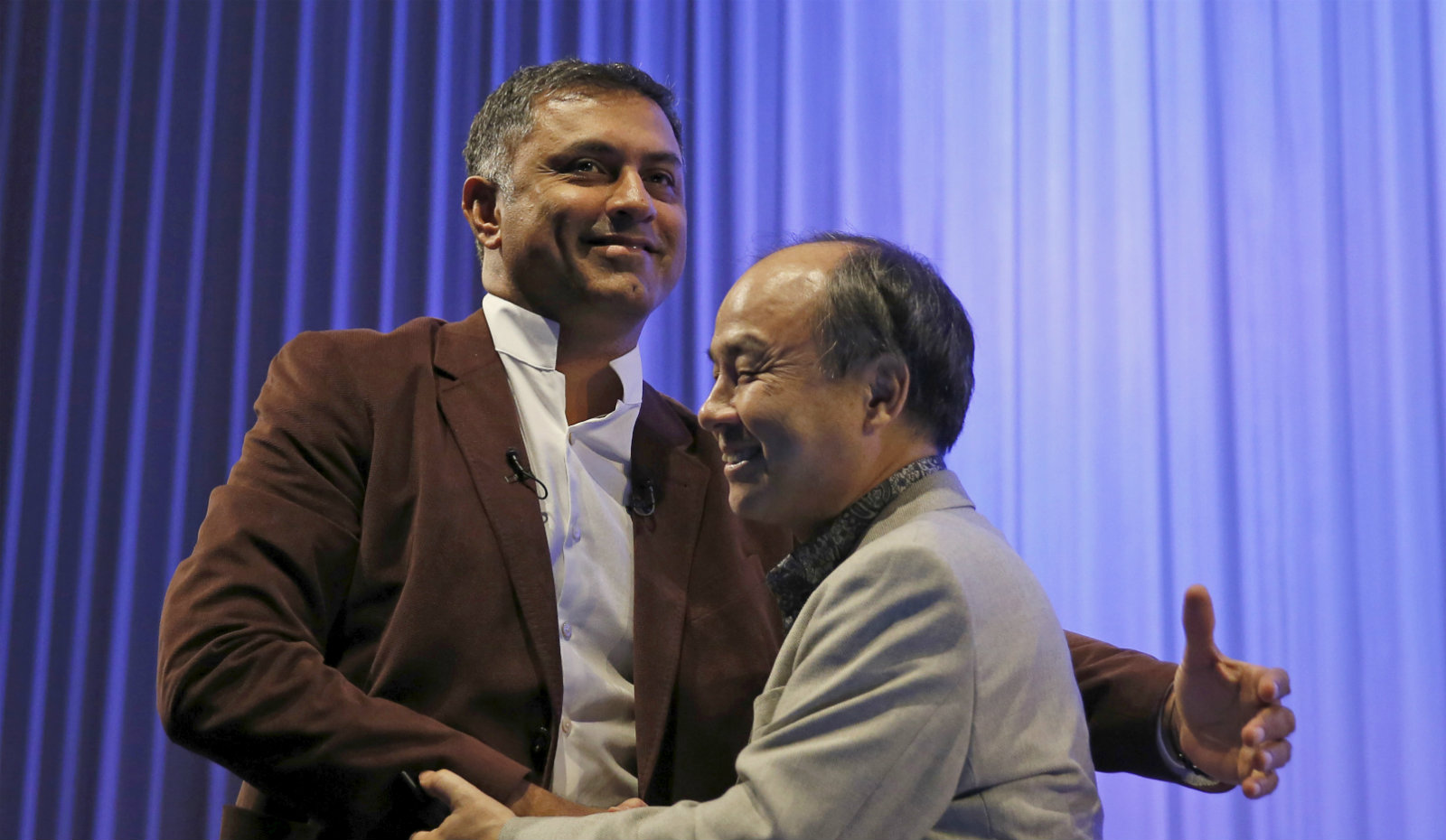 SoftBank Group Corp. Chairman and CEO Masayoshi Son (R) and President and COO Nikesh Arora shake hands during a special lecture of the SoftBank Academia in Tokyo, Japan October 22, 2015.