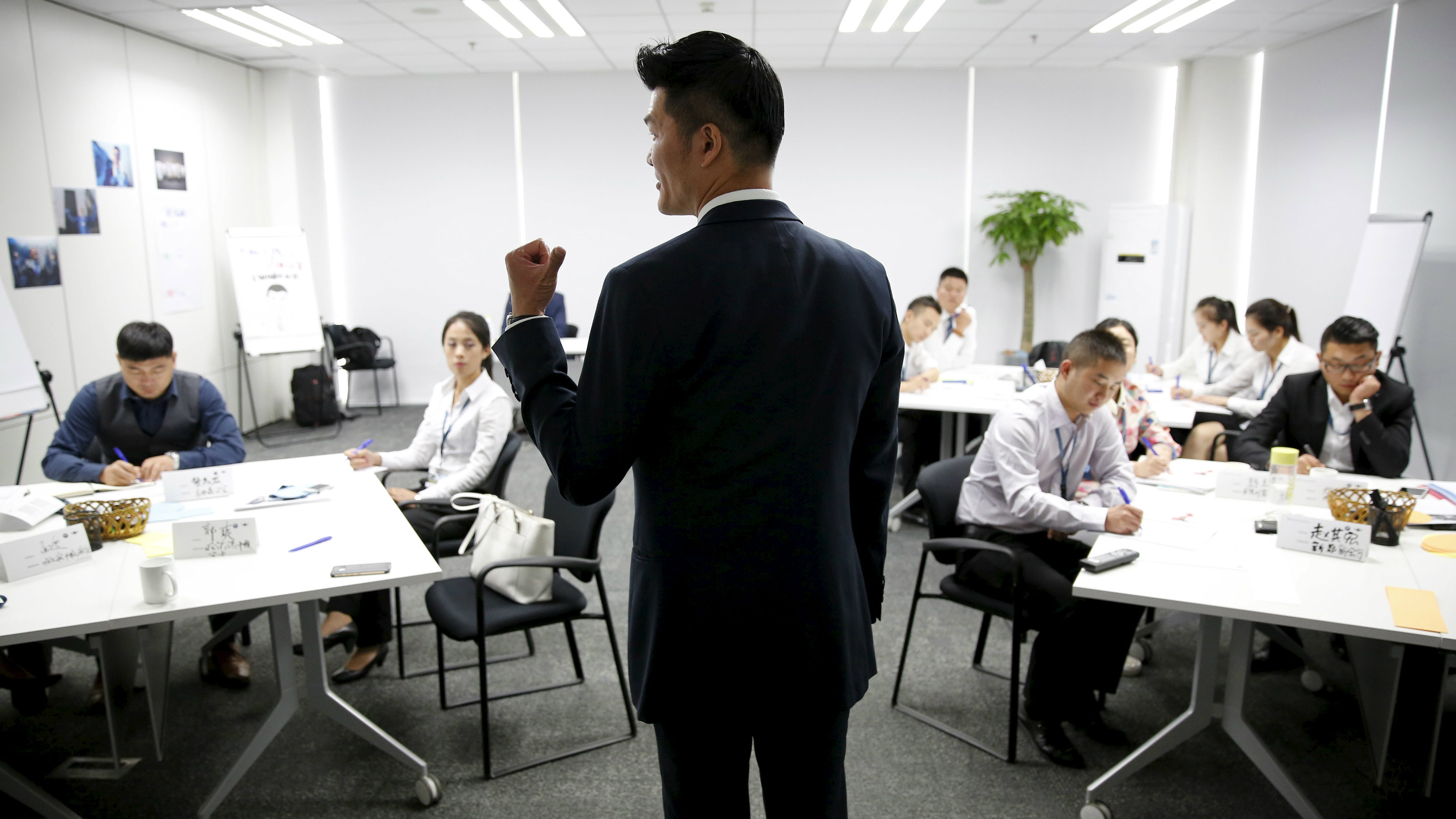 Trainer Lee Yida gives a lecture to dealership sales staffs during a sales camp at BMW Group Training Center in Beijing, China, September 9, 2015. At BMW, where deliveries to dealers in China have grown just 1 percent so far this year, this means putting recruits through sales 'boot camp' and turning experienced staff into spreadsheet wonks. The world's top luxury car maker this month opened its largest Asia training centre in Xi'an in Shaanxi province. It is also rolling out online training phone apps and having in-house trainers at dealerships look after basic skills so training centres can focus on teaching more advanced skills. Training classes have shifted to help dealers identify areas they can change for a quick improvement in results, said BMW's China training chief Xiao Yi. Picture taken on September 9, 2015. REUTERS/Kim Kyung-Hoon