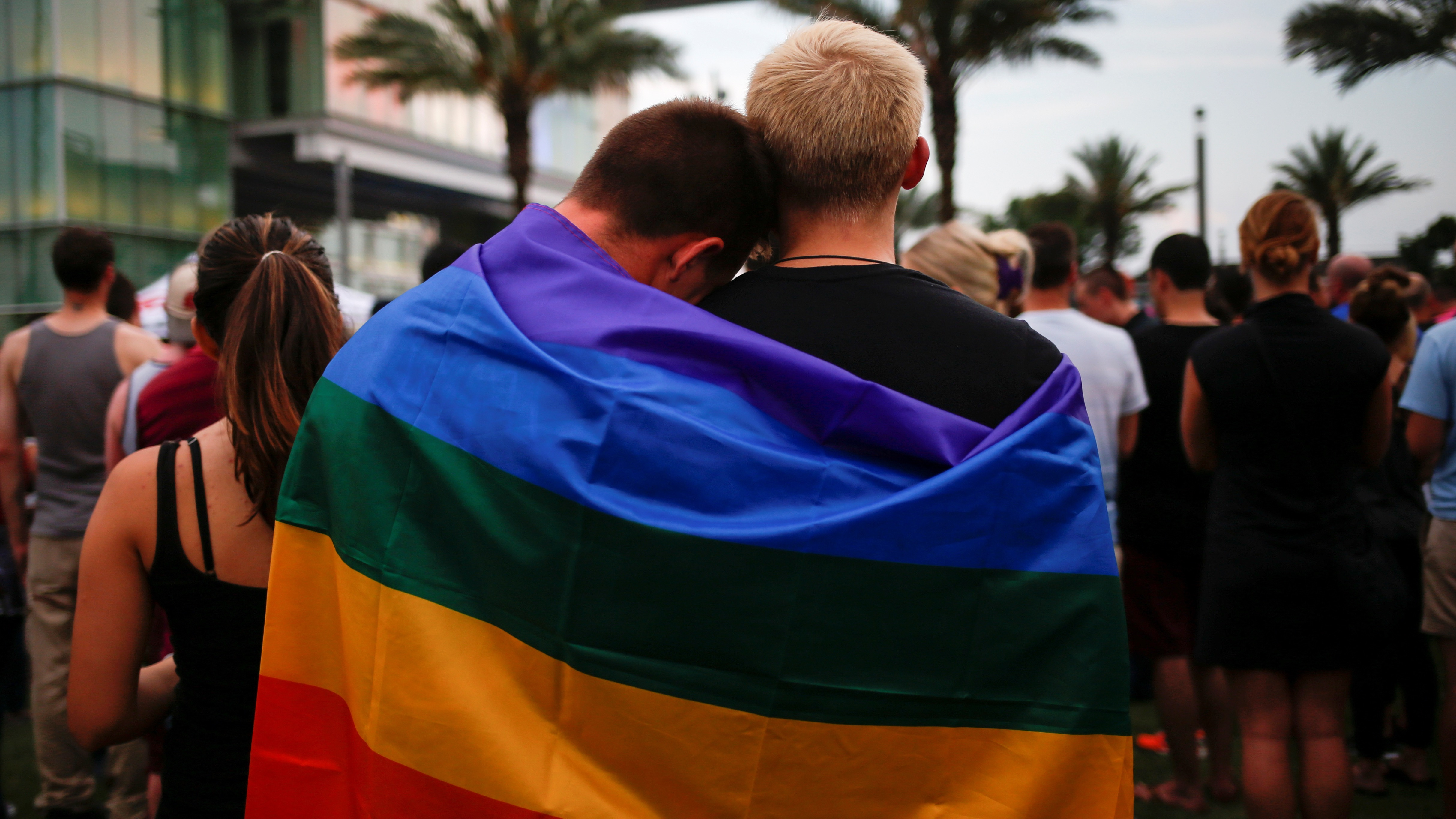 Men, draped in a rainbow flag, embrace ahead of a candle light vigil in memory of victims one day after a mass shooting at the Pulse gay night club in Orlando, Florida, U.S., June 13, 2016.  REUTERS/Adrees Latif - RTX2G2TO