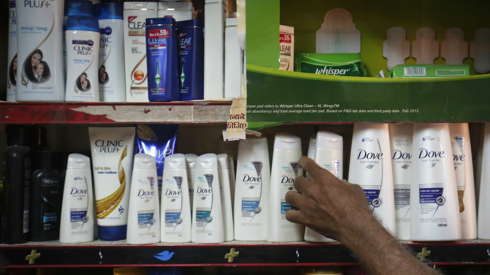 A salesman takes a bottle of Hindustan Unilever Limited (HUL) Dove shampoo from a shelf at a shop in Mumbai April 30, 2013. Unilever plans to pay up to $5.4 billion to raise its stake in its Indian subsidiary, making its biggest deal in 13 years a huge bet on the strength of demand for personal care and food products in Asia's third-largest economy.