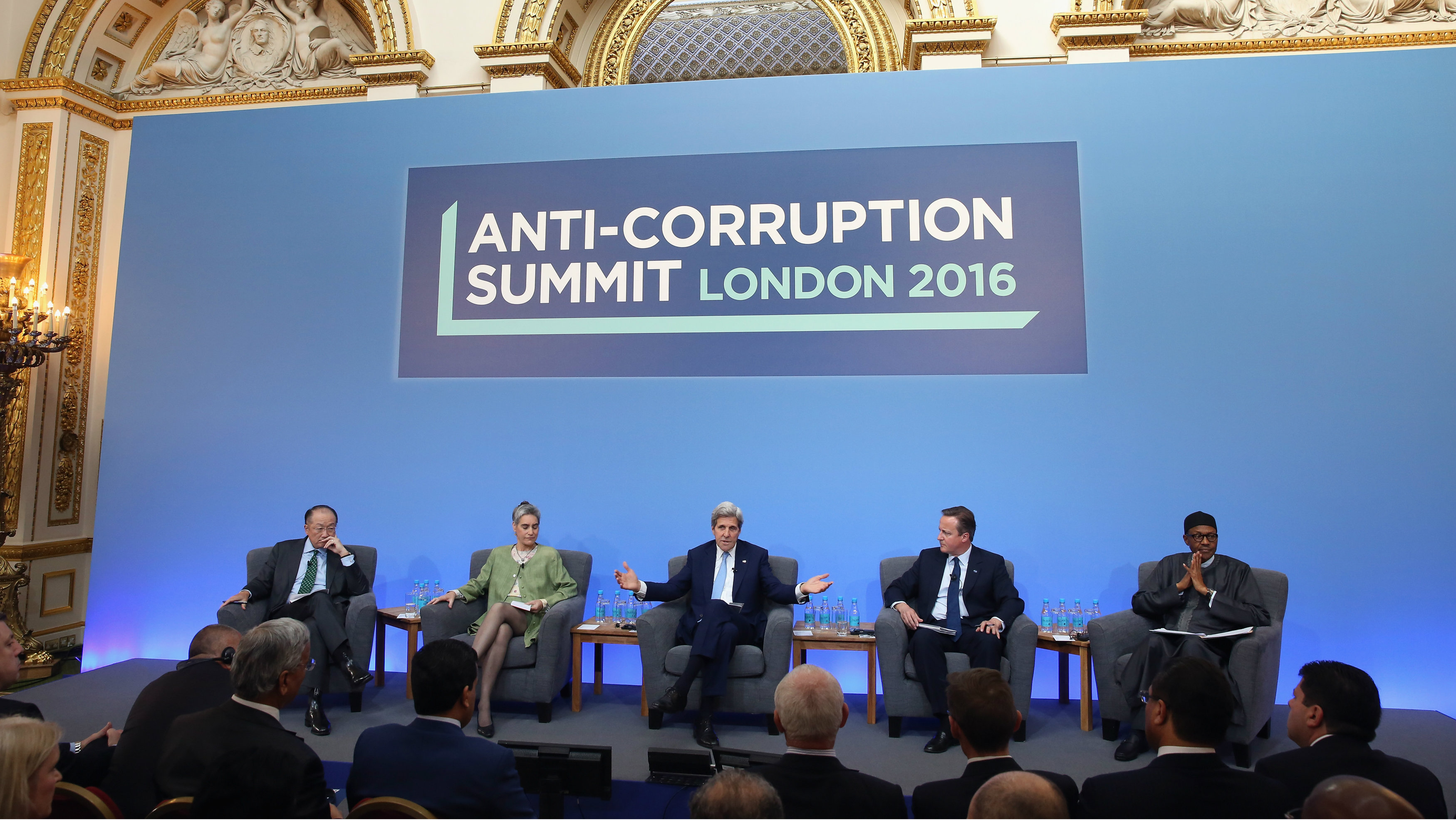 British Prime Minister Cameron is joined by Jim Yong Kim, President of the World Bank Group, (left) Sarah Chayes, a senior associate in the Democracy and Rule of Law Program, (second left) US Secretary of State John Kerry, (third from left) and Nigerian President Muhammadu Buhari, (right), as he opens the international anti-corruption summit on May 12, 2016 in London, England