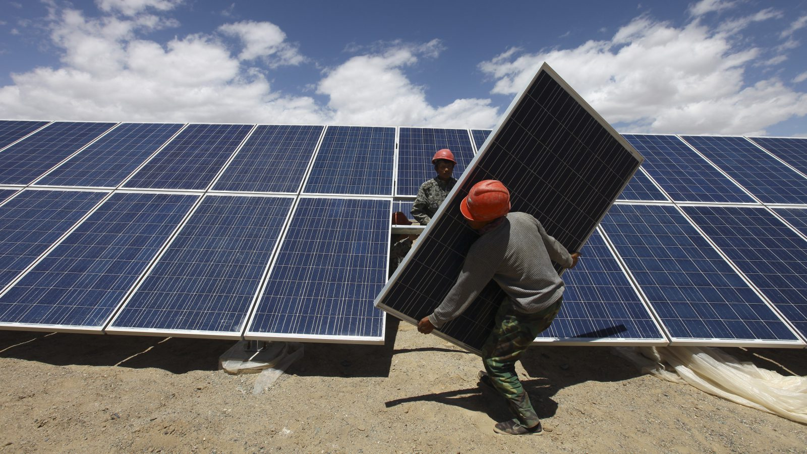 Workers install a solar panel in Jiuquan.