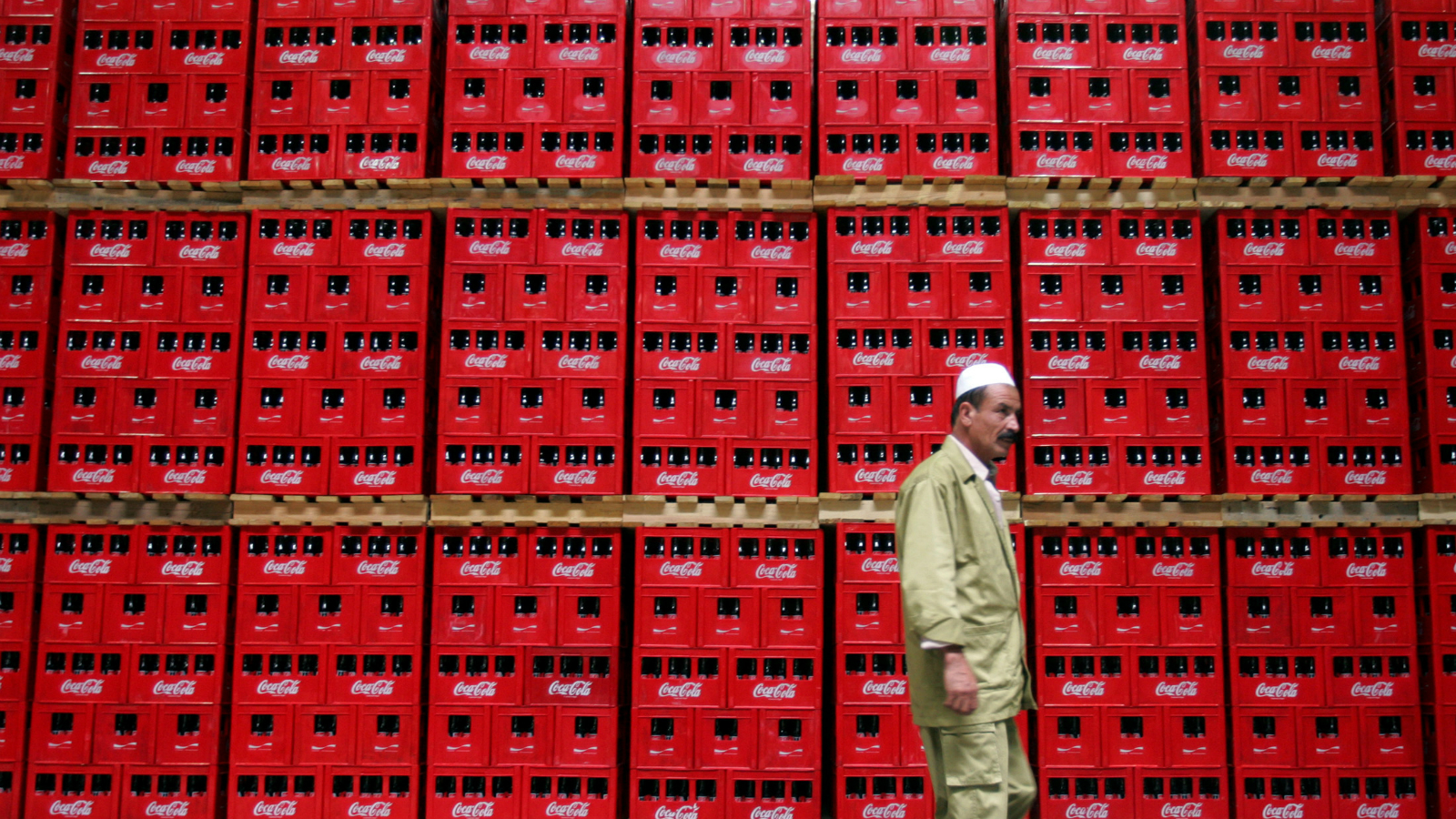 A worker walks in front of crates of Coca-Cola at the newly inaugurated bottling plant in Kabul September 10, 2006. Coca-Cola, with its distinctive red-and-white logo, has come to Kabul in what is at once a sign of economic progress and a symbol of the failure of major businesses to open up in the five years since the fall of the hardline Islamist Taliban.