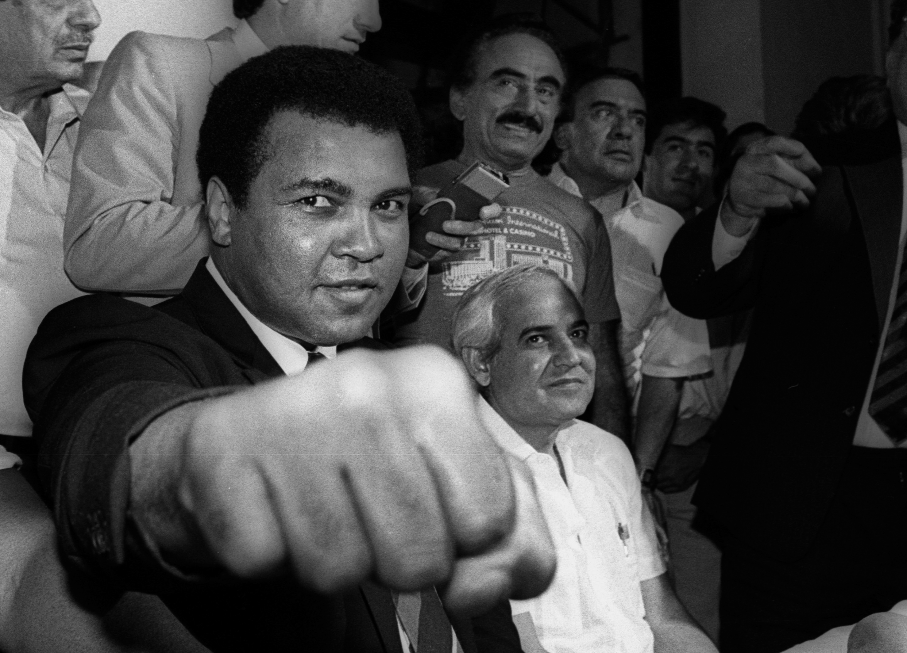 A smiling Muhammad Ali shows his fist to reporters during an impromptu press conference in Mexico City July 9, 1987.  - RTR1N6MB
