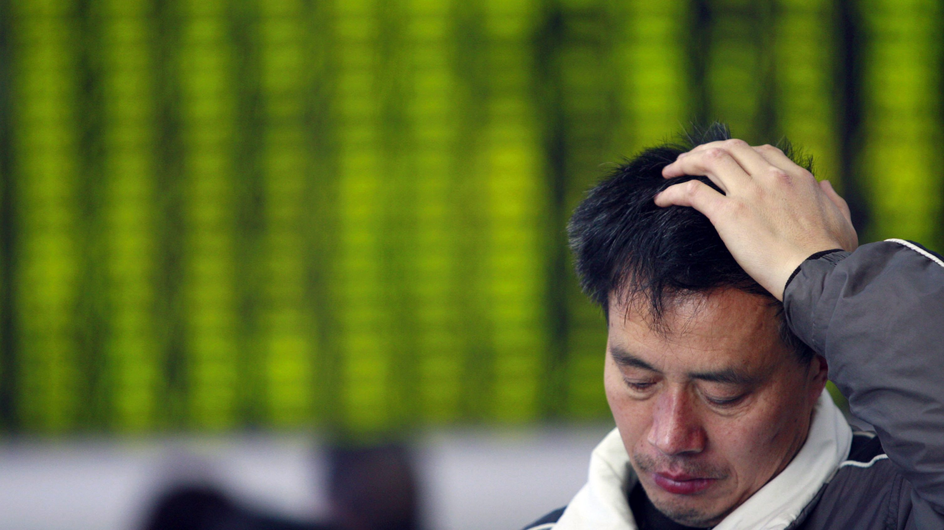 A man gestures in front an electronic board showing stock information at a brokerage house in Suining, Sichuan province March 17, 2008. China's main stock index ended down 3.6 percent on Monday at its lowest close in more than eight months, as already weak market sentiment took further blows from a tumble on Wall Street and a Chinese central bank warning of possible further monetary tightening.   REUTERS/Stringer (CHINA).  CHINA OUT. NO COMMERCIAL OR EDITORIAL SALES IN CHINA. - RTR1YEXD