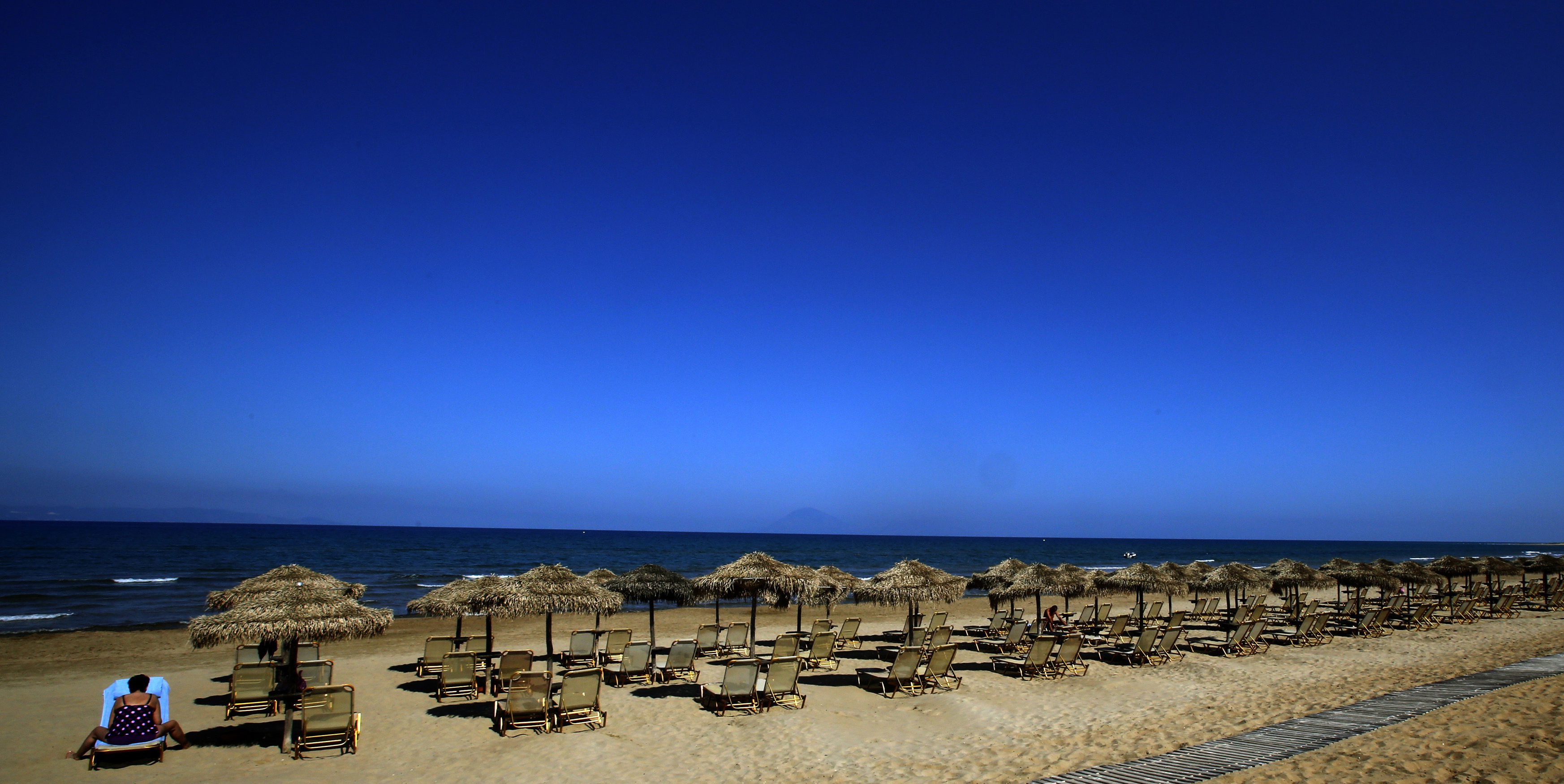 A German tourist sits on a sunbed on the beach of the Olympia Riviera resort in the town of Killini
