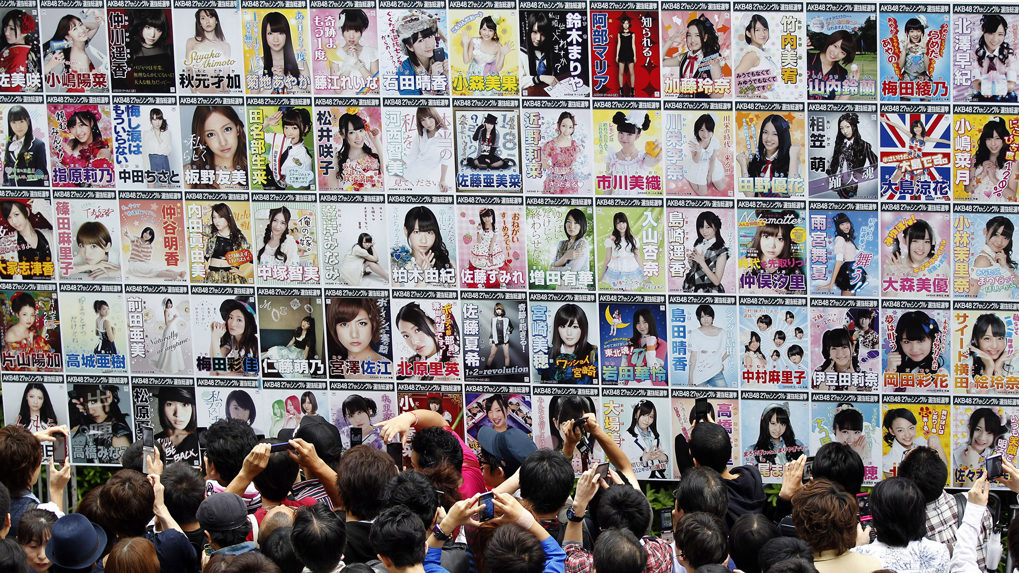 """Fans gather in front of """"election"""" posters, showing the contestants for the new leader of Japan's girl pop group AKB48, ahead of an annual popularity """"election"""" event at Tokyo's Budokan gymnasium June 6, 2012. In a three-hour show broadcast live from Tokyo's hallowed Budokan, 23-year-old Yuko Oshima was selected as leader and face of the group, which has been recognized by Guinness as the world's biggest girl pop group. AKB48 was founded in 2005, and is known for its perky routines and high """"kawaii,"""" or cuteness, quotient. Every year, fans vote to determine 64 of the most popular girls out of a 237-member pool who are then rotated in and out of four main troupes and several affiliated groups according to their popularity. Picture taken June 6, 2012. To match story JAPAN-MUSIC/AKB48     REUTERS/Yuriko Nakao (JAPAN - Tags: ENTERTAINMENT SOCIETY) - RTR339JZ"""