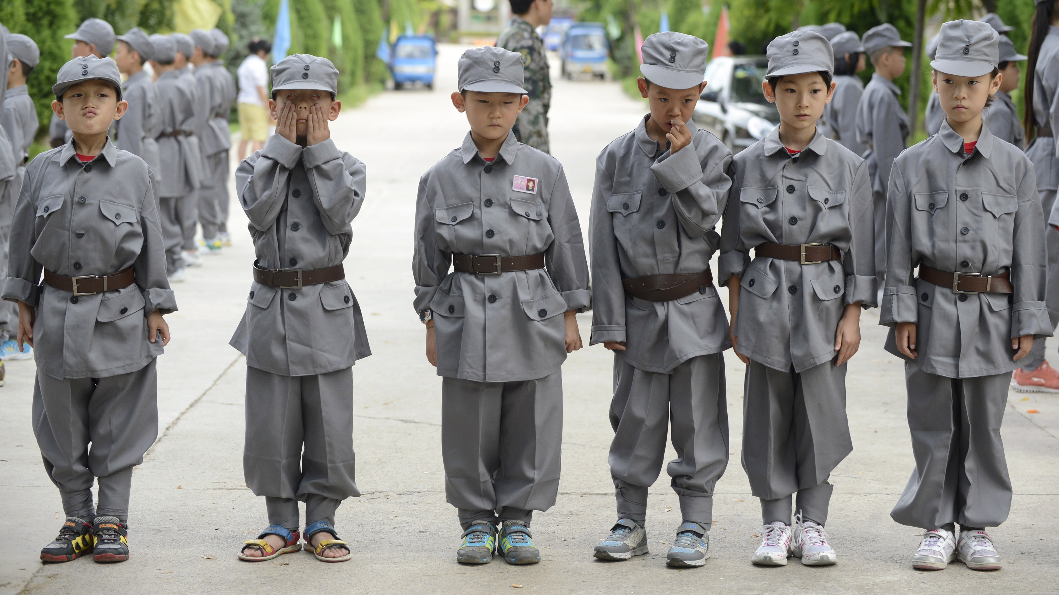 Primary school students in Red Army uniforms react as they take part in military formation training during camp in Taiyuan