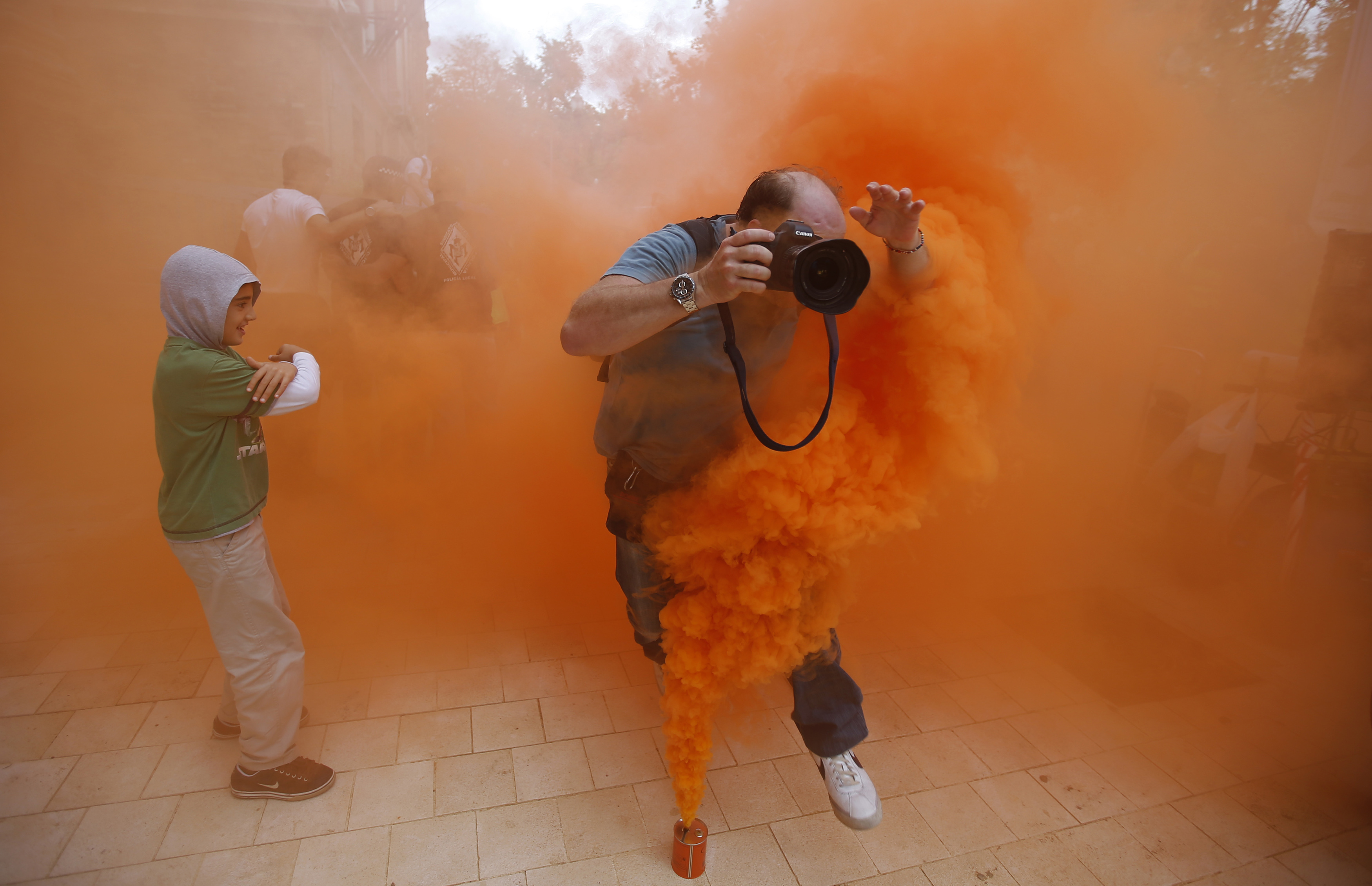 A photographer jumps over a smoke canister