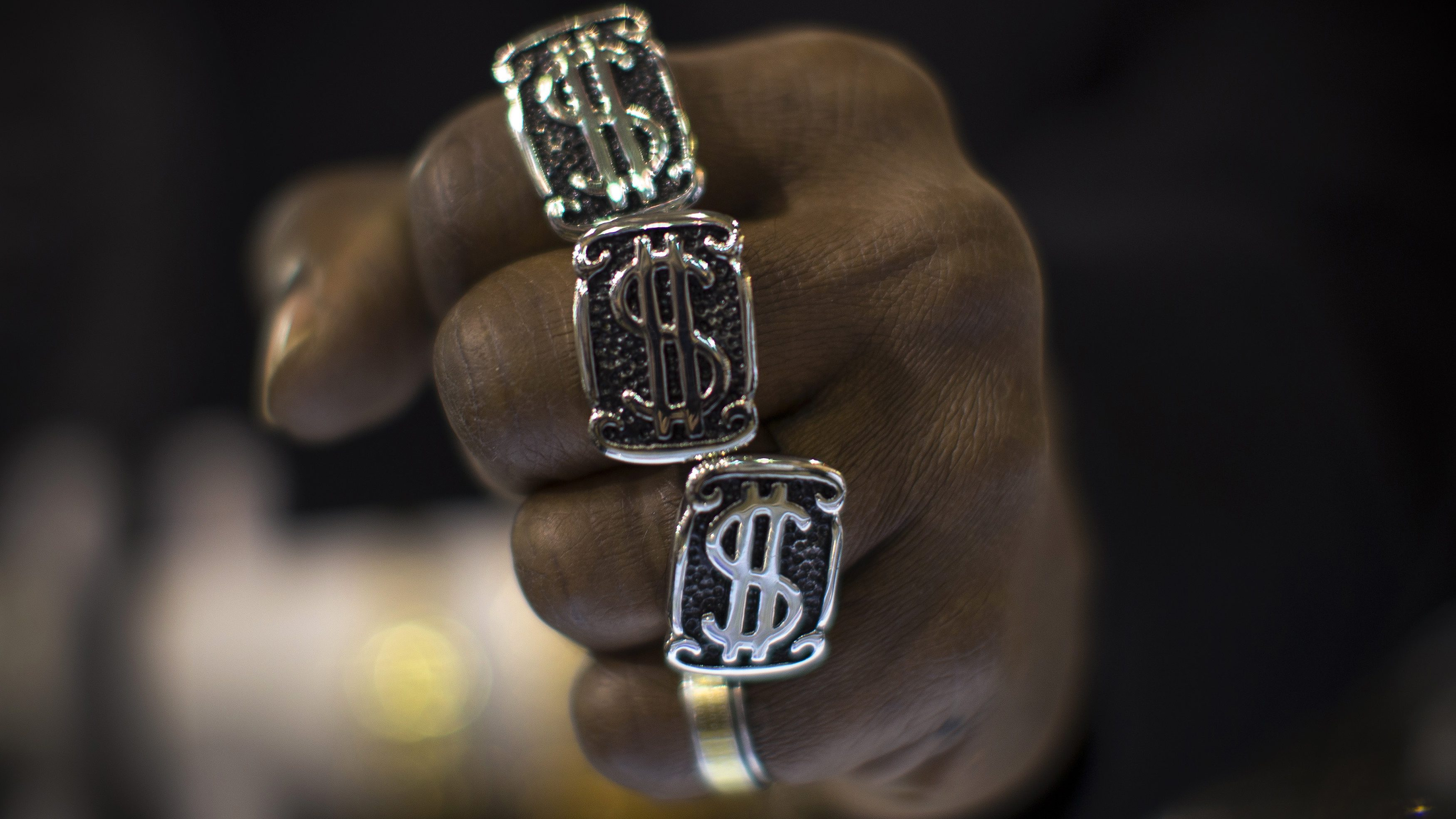A man wears U.S. dollar sign rings in a jewellery shop in Manhattan in New York City November 6, 2014. A year-long investigation into allegations of collusion and manipulation by global currency traders is set to come to a head on Wednesday, with Britain's financial regulator and six big banks expected to agree a settlement involving around ?1.5 billion ($2.38 billion) in fines. The settlement comes amid a revival of long-dormant volatility on the foreign exchanges, where a steady rise of U.S. dollar this year has depressed oil prices and the currencies of many commodity exporters such as Russia's rouble, Brazil's real and Nigeria's naira - setting the scene for more turbulence on world financial markets in 2015.  Picture taken November 6, 2014.