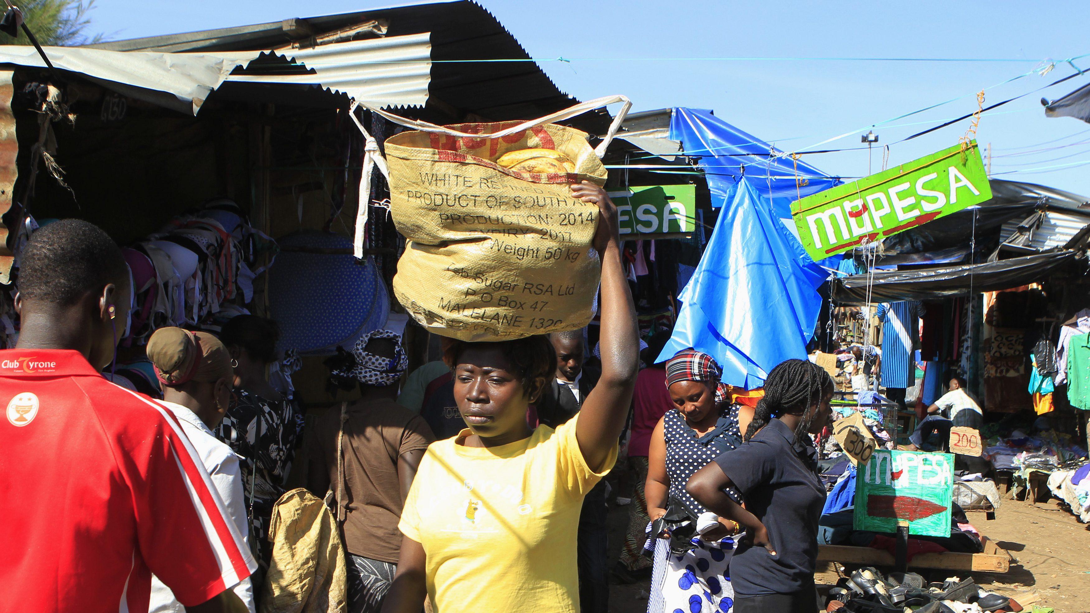 Kibera residents walk past an M-Pesa banner at an open-air market in Kenya's capital Nairobi