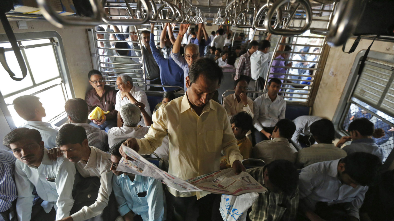 A man reads the newspaper as he commutes to work by a local train in Mumbai February 25, 2015. India's railway budget, to be presented later on Thursday, will signal the direction of long-term reforms needed to revamp the world's fourth-largest rail network, Railway Minister Suresh Prabhu said. Picture taken February 25, 2015.