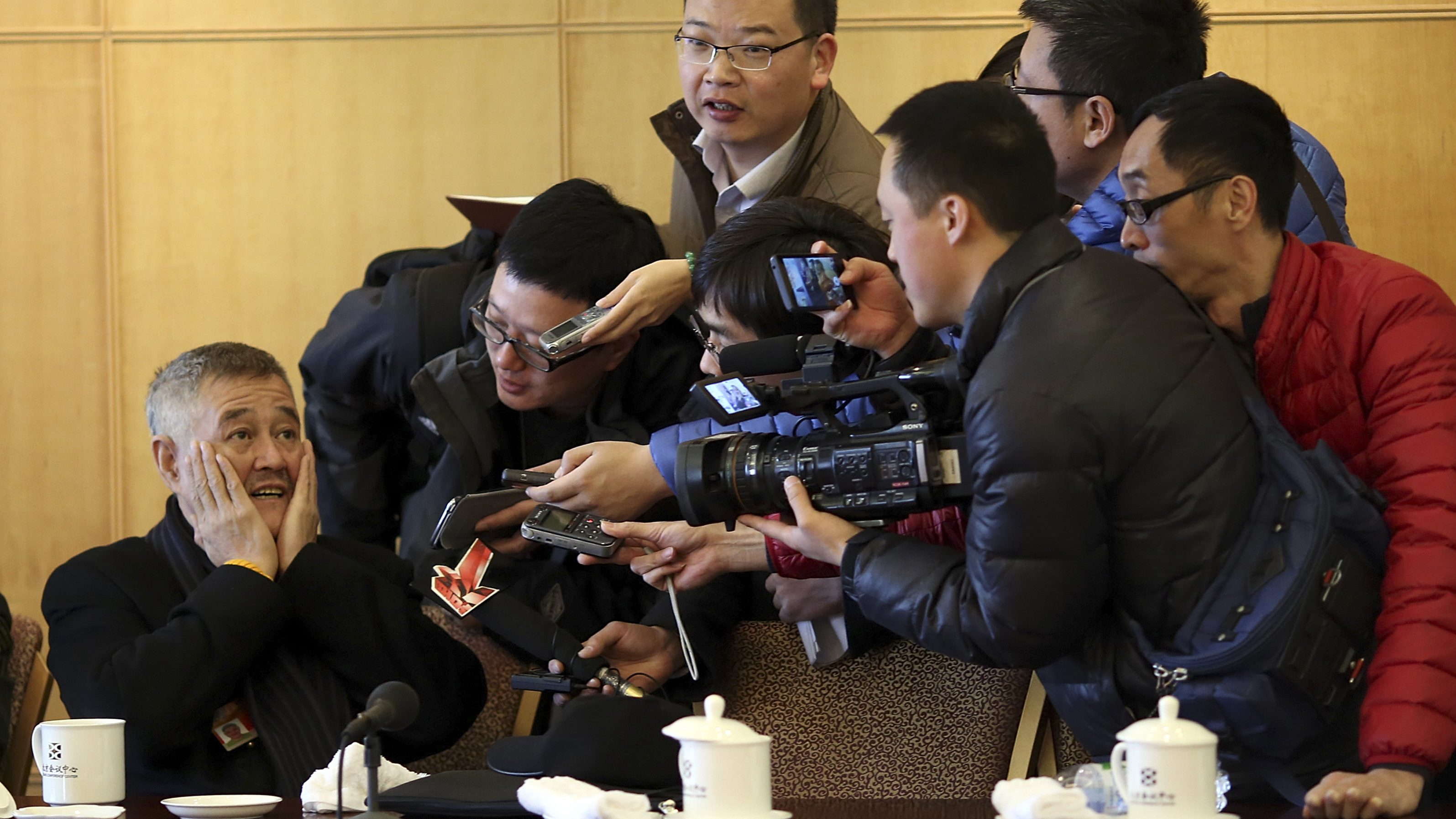 Actor Zhao Benshan (L), also a delegate of Chinese People's Political Consultative Conference (CPPCC), wipes his face as he talks to journalists during a session of the CPPCC, in Beijing, March 4, 2015. REUTERS/Stringer (CHINA - Tags: POLITICS ENTERTAINMENT SOCIETY TPX IMAGES OF THE DAY) CHINA OUT. NO COMMERCIAL OR EDITORIAL SALES IN CHINA - RTR4RYYZ