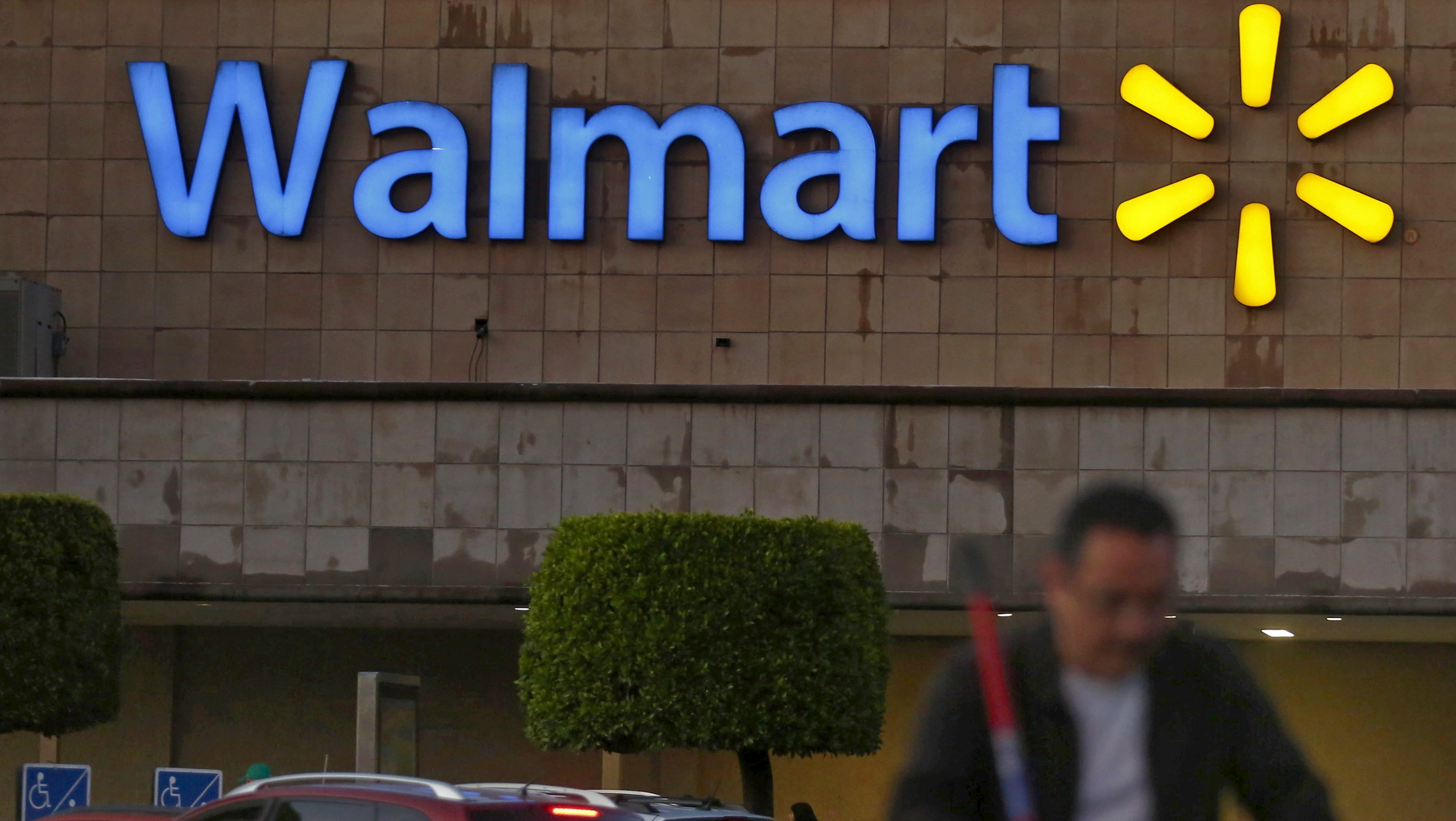 A shopper pushes a cart in front of a Wal-Mart store in Mexico City