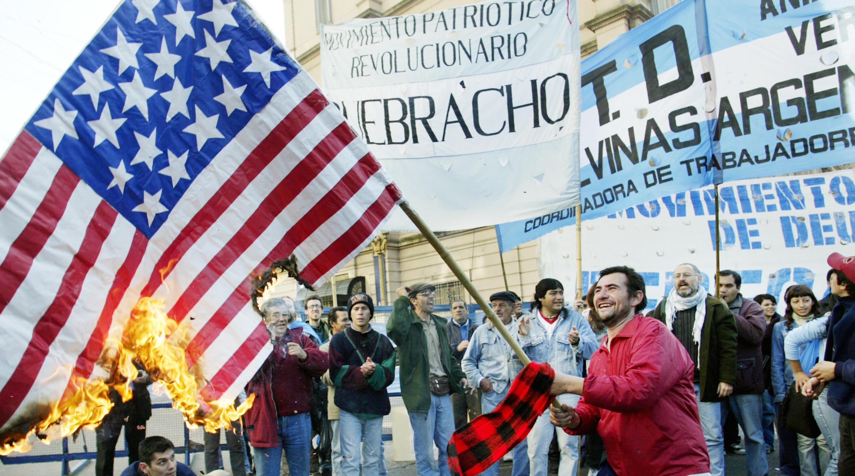 DEMONSTRATORS BURN A US FLAG PROTESTING AGAINST IMF VISIT TO ARGENTINA.
