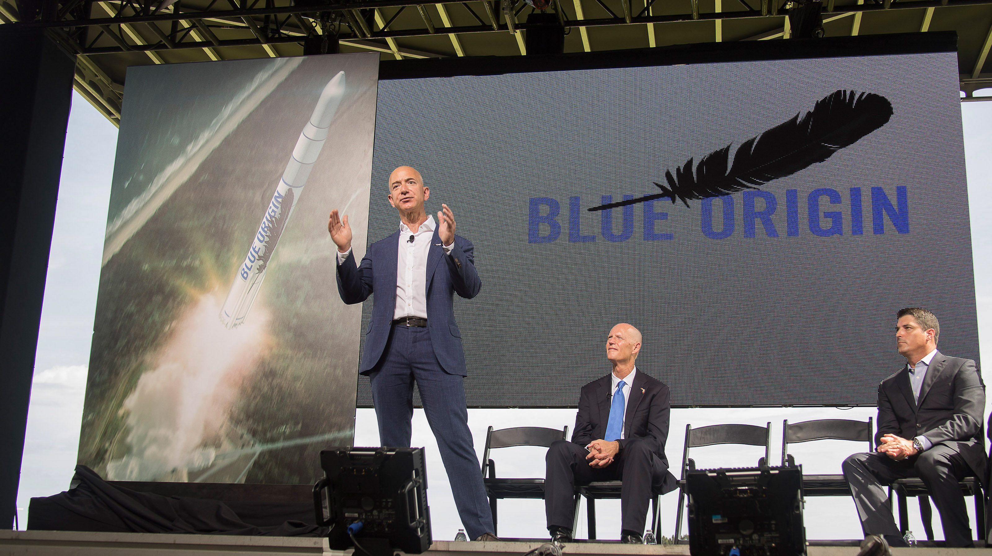 Amazon founder and Blue Origin founder Jeff Bezos (L)announces plans to build a rocket manufacturing plant and launch site at Cape Canaveral Air Force Station, Florida September 15, 2015. Governor Rick Scott and Steve Crisafulli, Speaker of the Florida House of Representatives (R) look on.  HO/Mike Brown/Space Florida THIS IMAGE HAS BEEN SUPPLIED BY A THIRD PARTY. IT IS DISTRIBUTED, EXACTLY AS RECEIVED BY REUTERS, AS A SERVICE TO CLIENTS. FOR EDITORIAL USE ONLY. NOT FOR SALE FOR MARKETING OR ADVERTISING CAMPAIGNS - RTS18ZV
