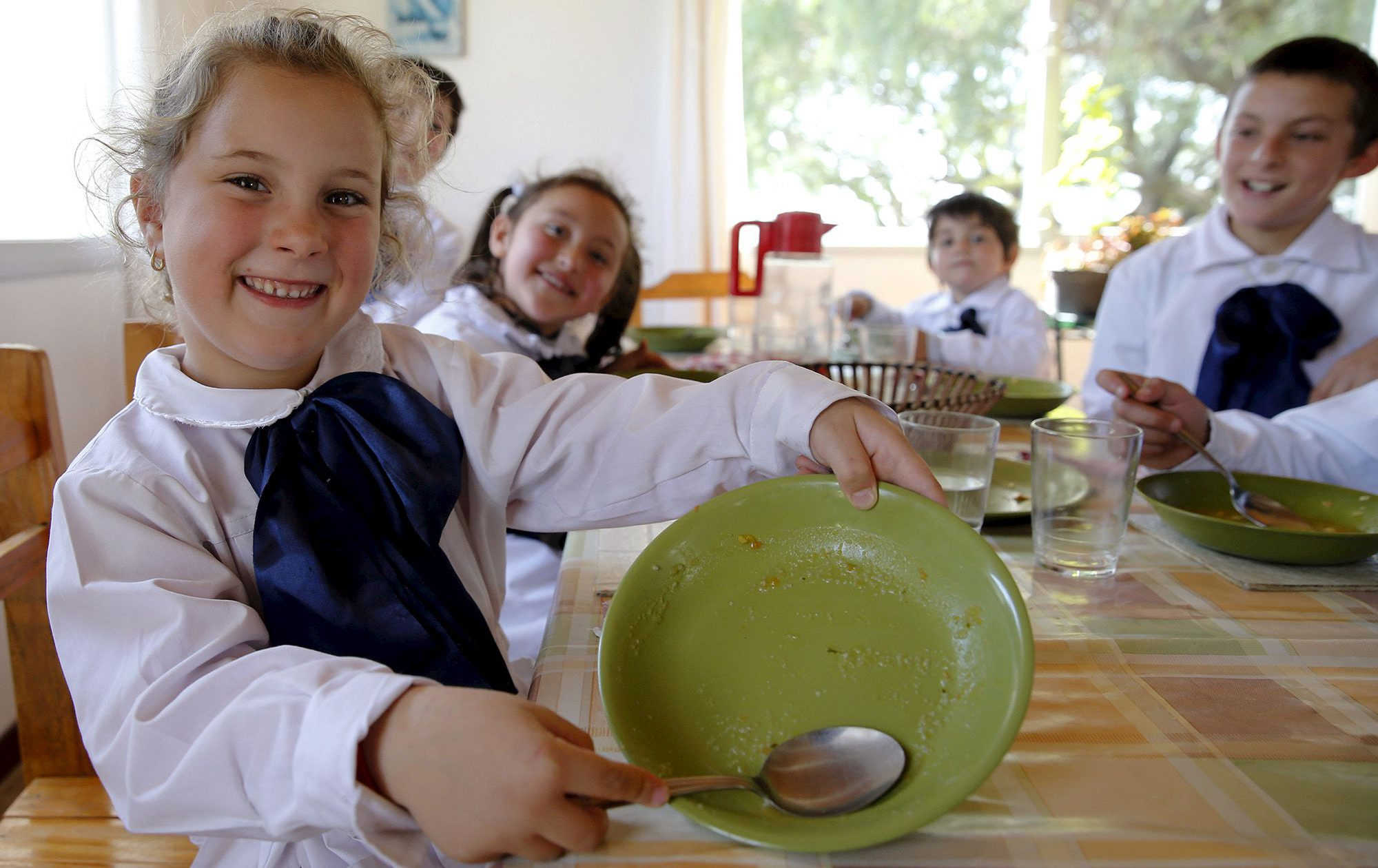Students eat lunch that was prepared with vegetables grown by themselves at the Agustin Ferreira farm school near Minas city, in the northeast of Montevideo, September 15, 2015. The school has 12 students aged 4 to 11, with only one teacher, and incorporates activities such as milking a cow, planting vegetables and cooking to improve the education of the children. REUTERS/Andres Stapff - RTS1AVT