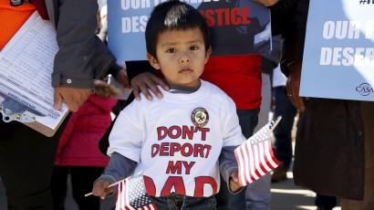 A young boy holds U.S. flags as immigrants and community leaders rally in front of the U.S. Supreme Court to mark the one-year anniversary of President Barack Obama's executive orders on immigration in Washington