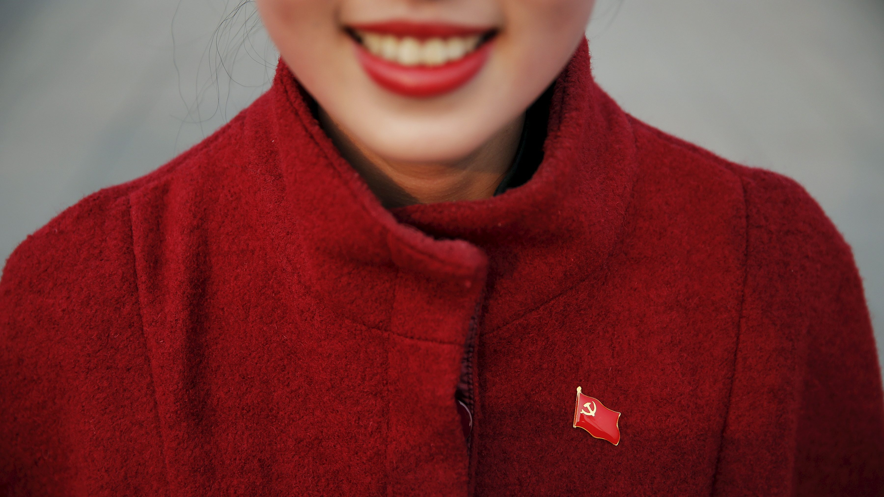 A hostess wears a pin of China's Communist Party flag ahead of the closing ceremony of National People's Congress at the Great Hall of the People in Beijing