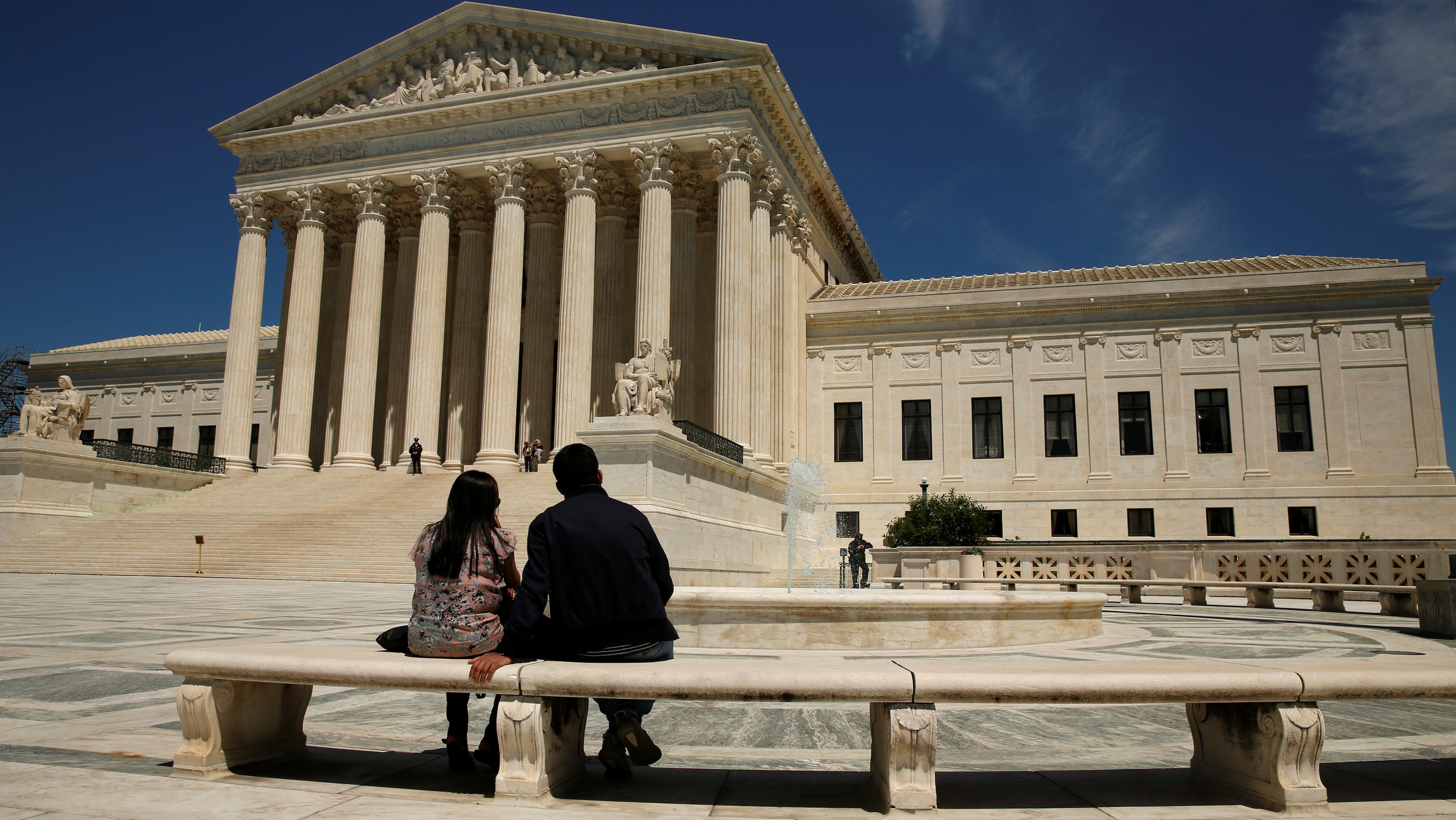 A couple sit in front of the U.S. Supreme Court in Washington May 16, 2016. REUTERS/Kevin Lamarque - RTSEKC1