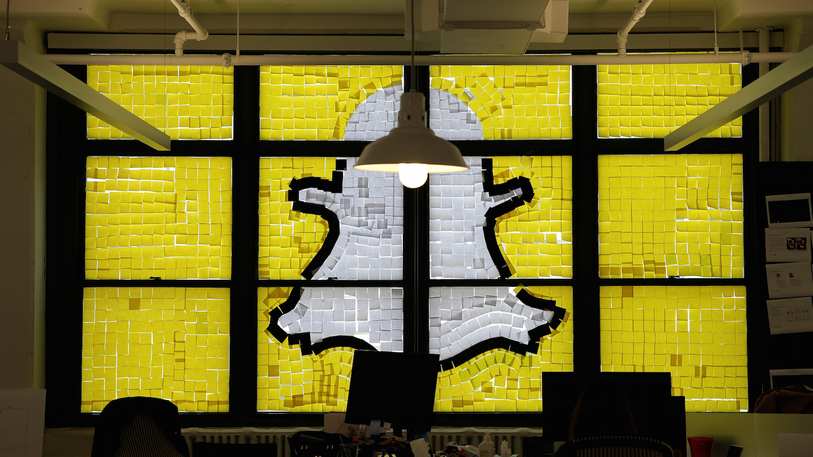 "An image of the Snapchat logo created with Post-it notes is seen in the windows of Havas Worldwide at 200 Hudson Street in lower Manhattan, New York, U.S., May 18, 2016, where advertising agencies and other companies have started what is being called a ""Post-it note war"" with employees creating colorful images in their windows with Post-it notes."