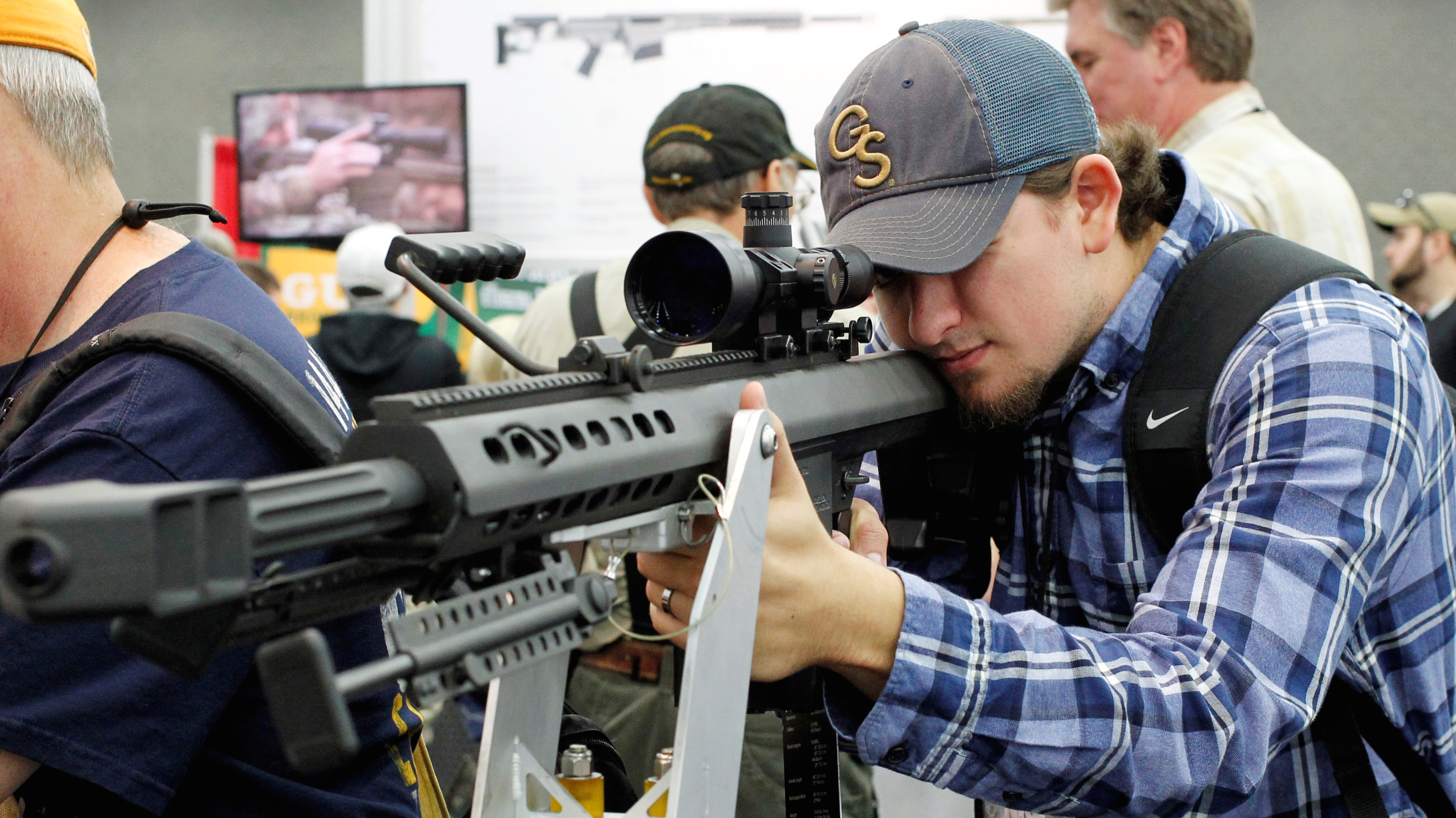 Brannan Ganas looks over guns at the Barrett Firearms booth at the National Rifle Association's annual meetings and exhibits show in Louisville