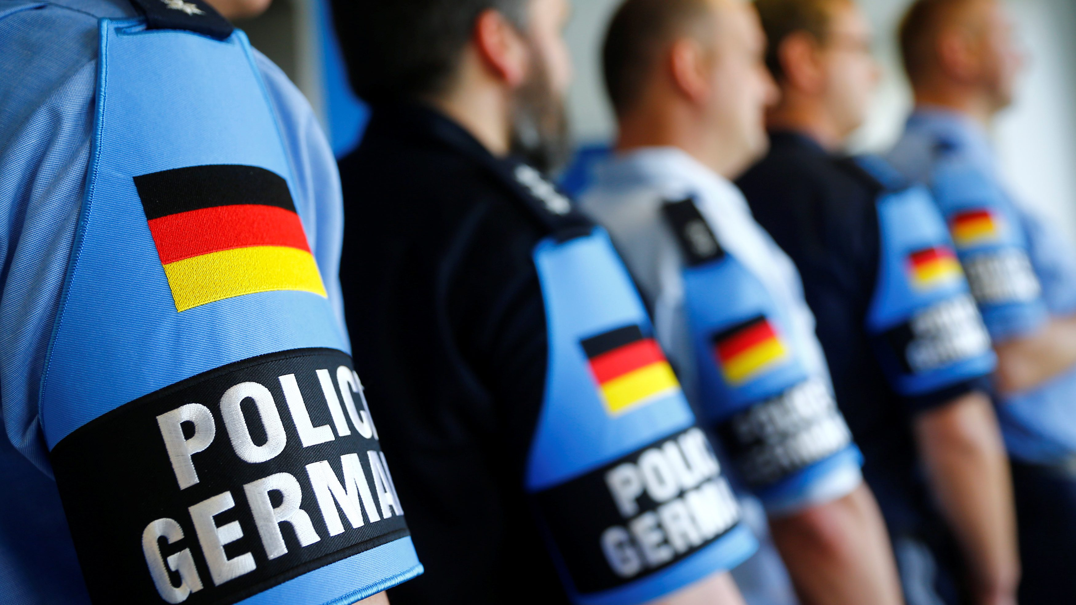 """German police officers pose for an image with their armband reading """"Police Germany"""" at the North Rhine-Westphalian police headquarters in Duisburg, Germany, June 6, 2016. Germany is sending 12 police officers from eight different German federal states who know the local soccer hooligans scene to support French police during the upcoming EURO 2016 soccer championships in France.      - RTSG7F3"""