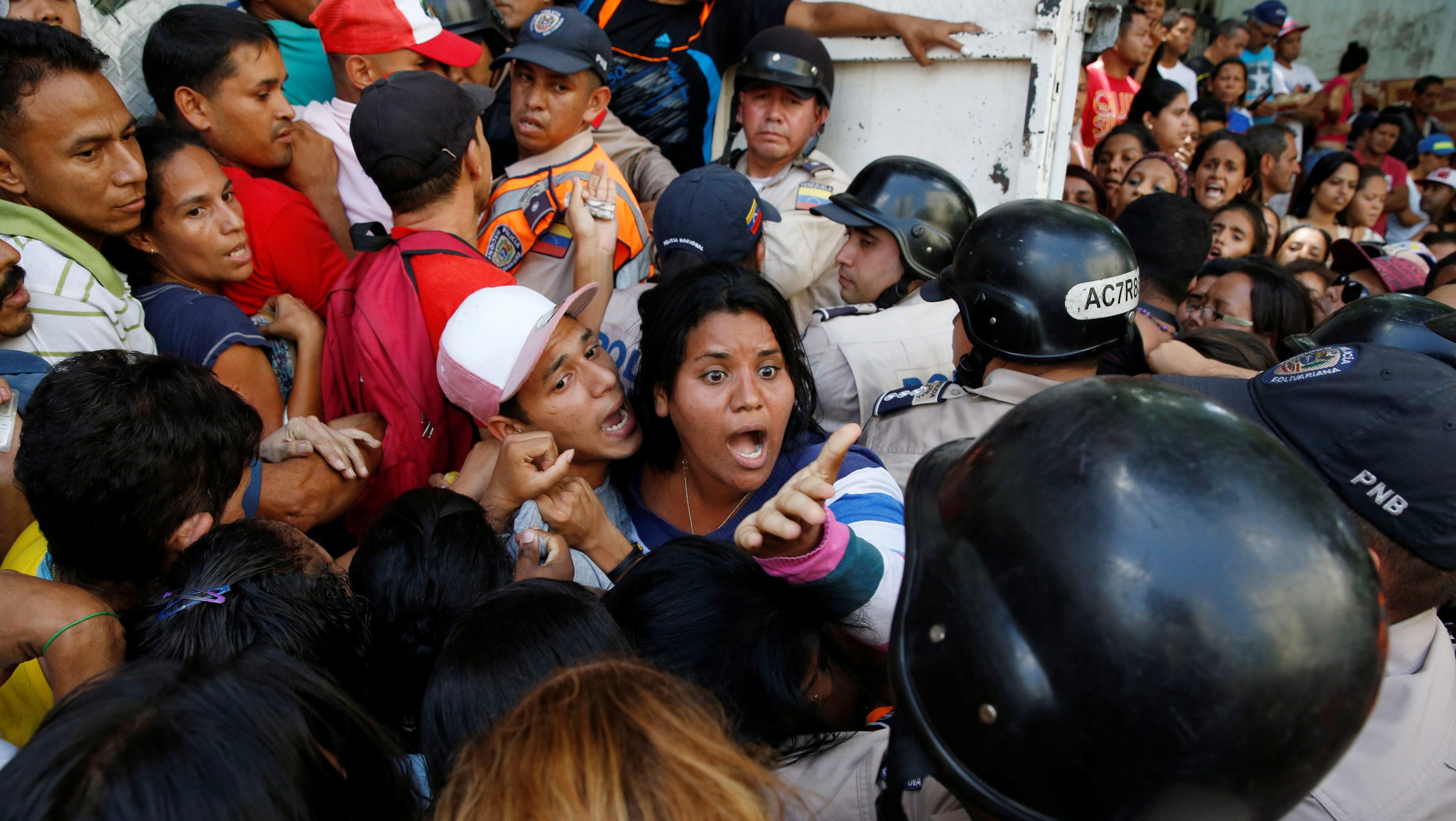 People gather to try to buy pasta while riot police try to control the crowd outside a supermarket in Caracas