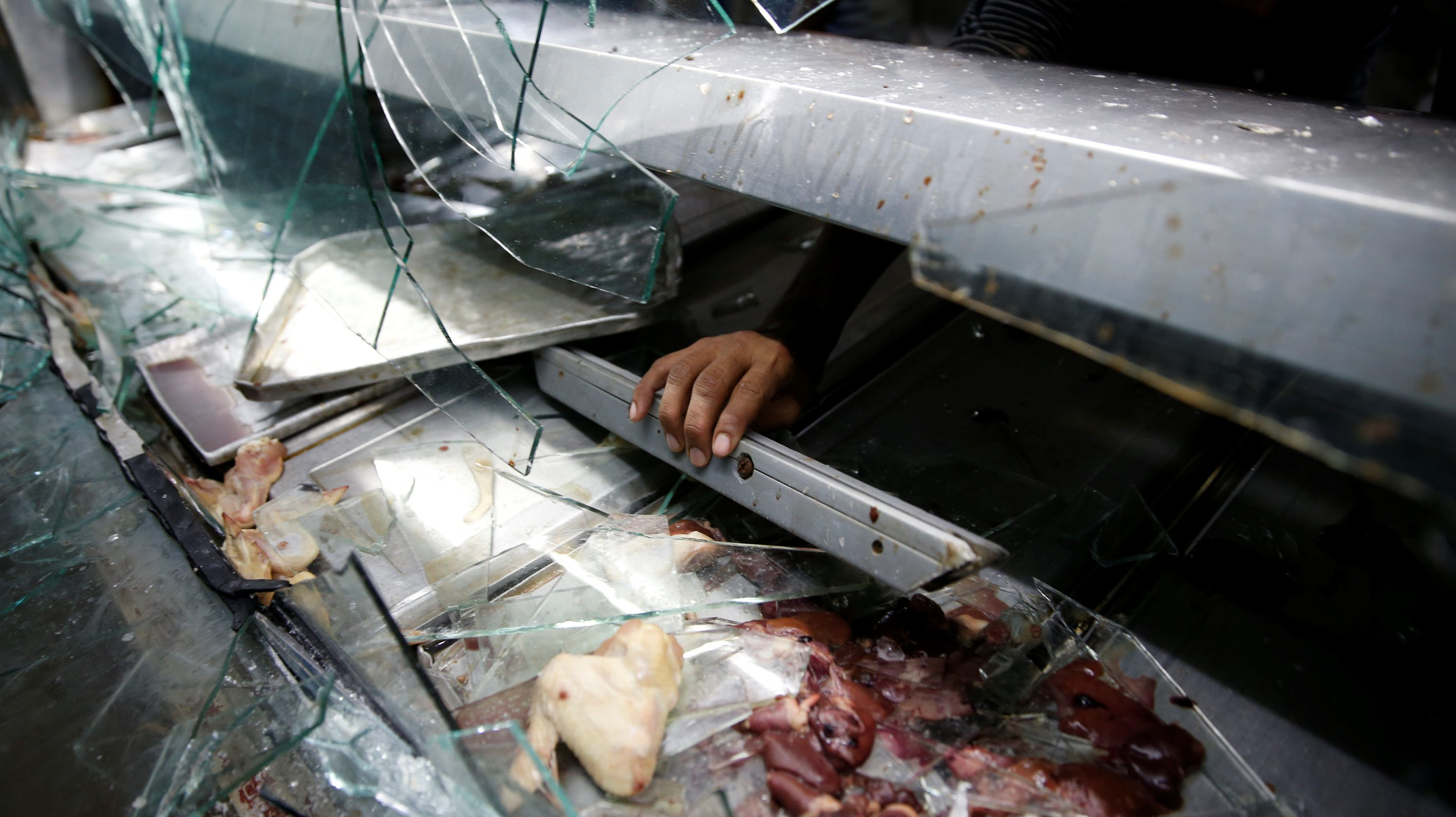 A man grabs a piece of a broken refrigerator, after a butcher's stall was looted in the slum of Petare in Caracas