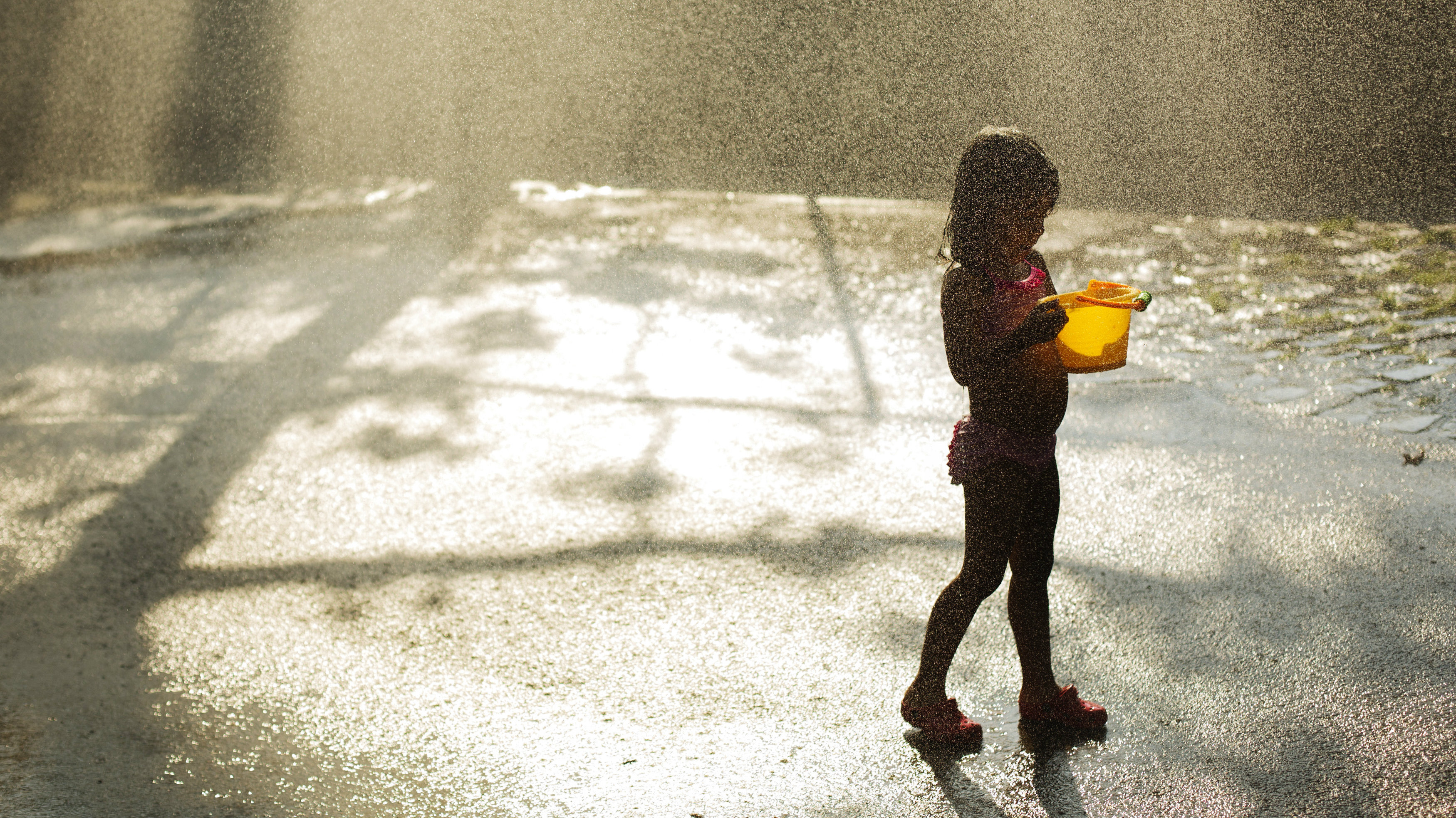 A girl plays as she cools off in a sprinkler system installed inside a playground during a hot summer day in New York, July 17, 2013.